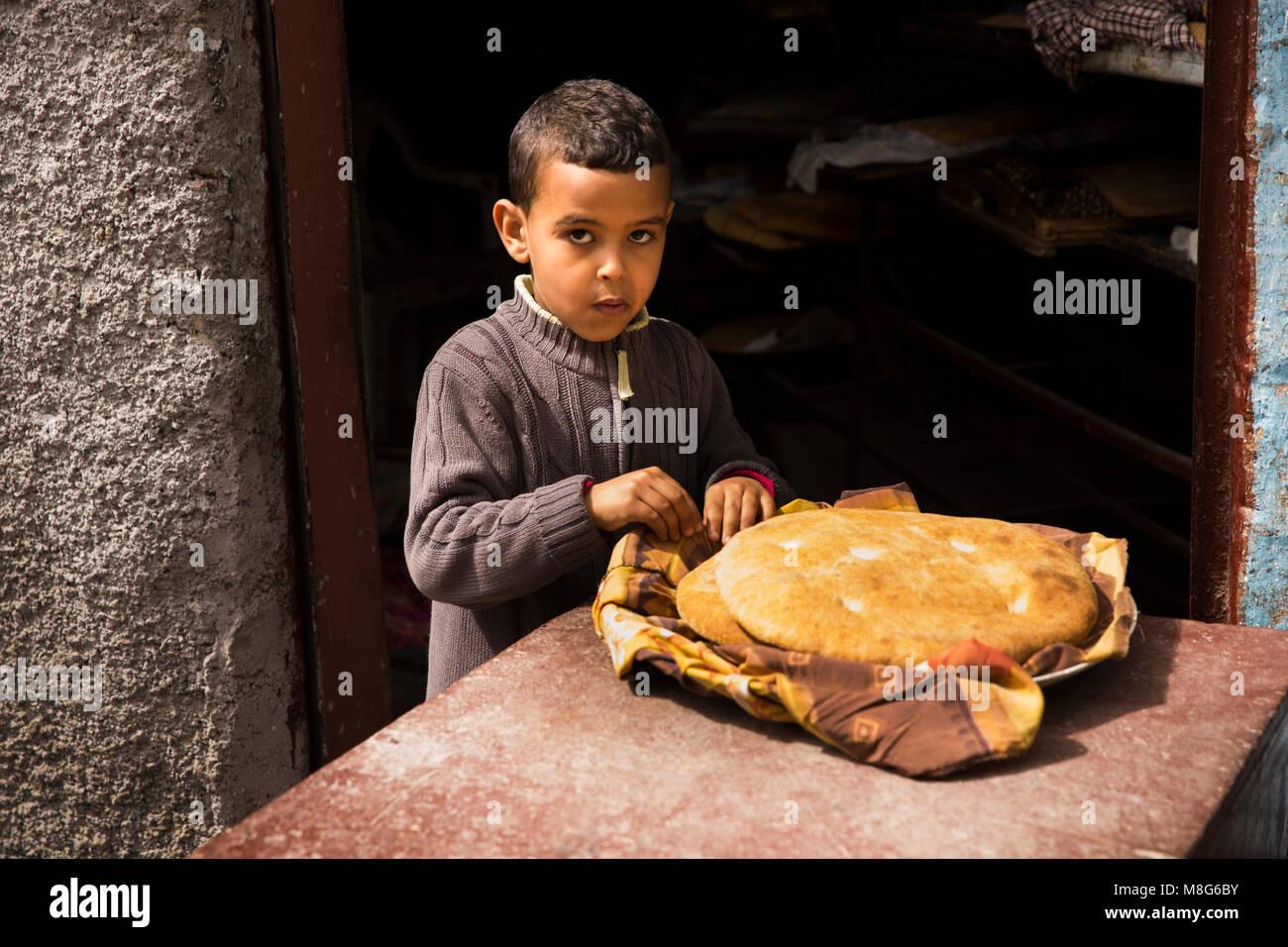 Il Marocco, Casablanca, Medina, Rue Tnaker, ragazzo di mangiare pane appena sfornato pagnotta di pane Immagini Stock