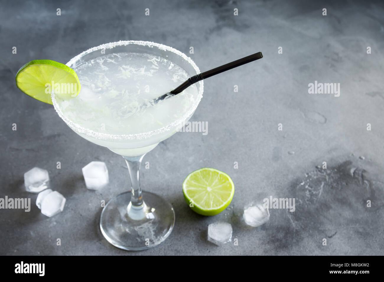 Margarita Сocktail con calce e ghiaccio sul cemento grigio sfondo, copia dello spazio. Classic Margarita o Daiquiry Immagini Stock