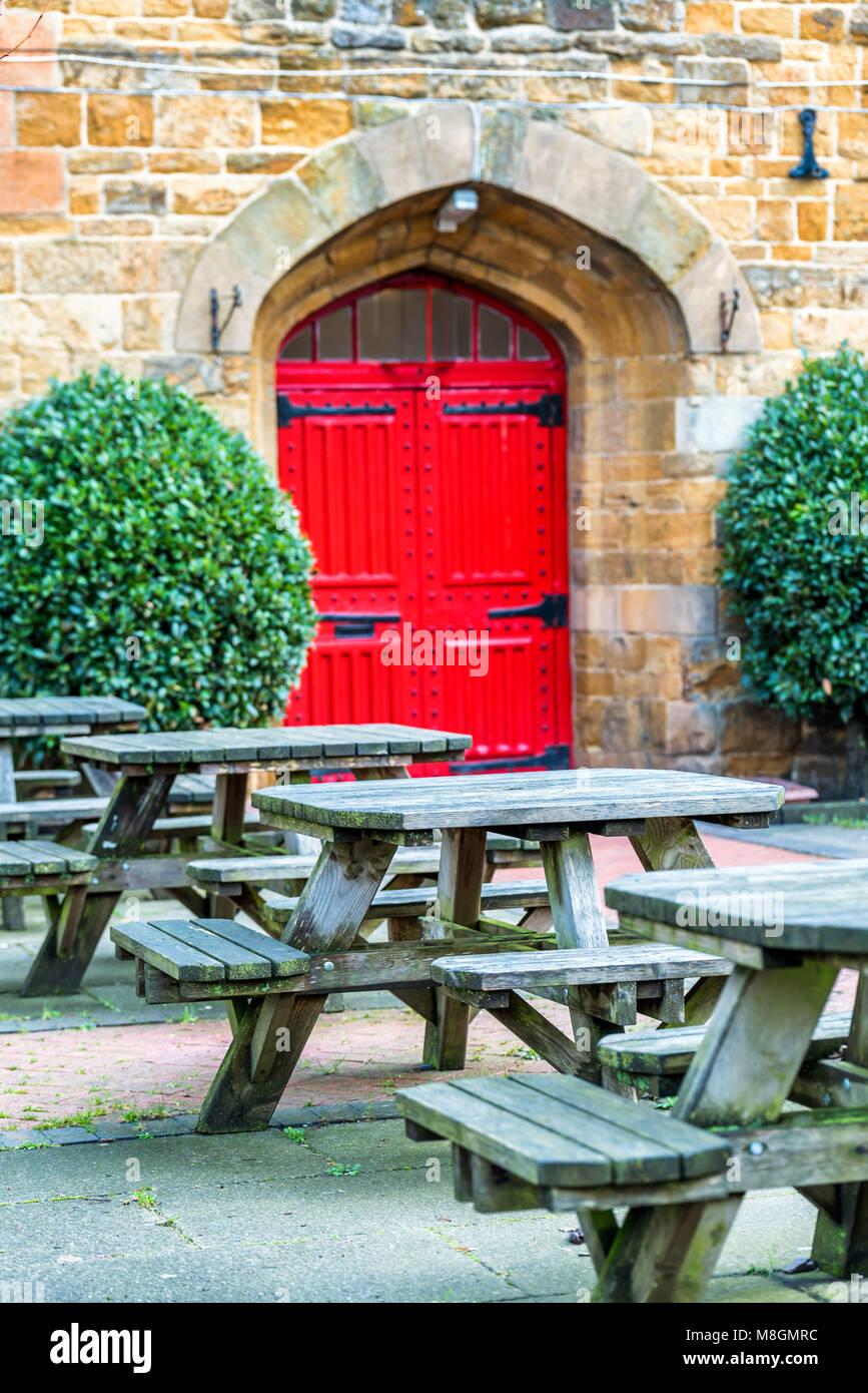Foto Di Porte Antiche vista giorno di vuoto tipico pub giardino con tavoli e rosso