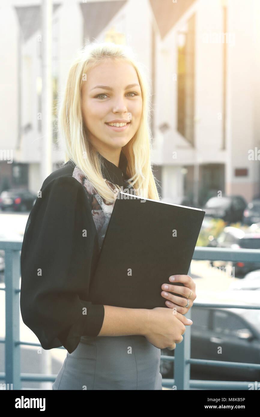 Giovane donna di affari con appunti in piedi sul balcone dell'ufficio Immagini Stock