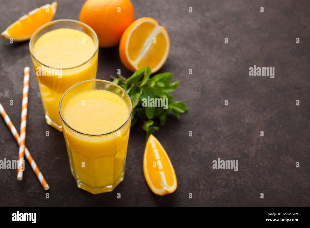 Due bicchieri di succo d'arancia appena spremuto e menta su un colore marrone scuro dello sfondo. Vista da sopra Immagini Stock