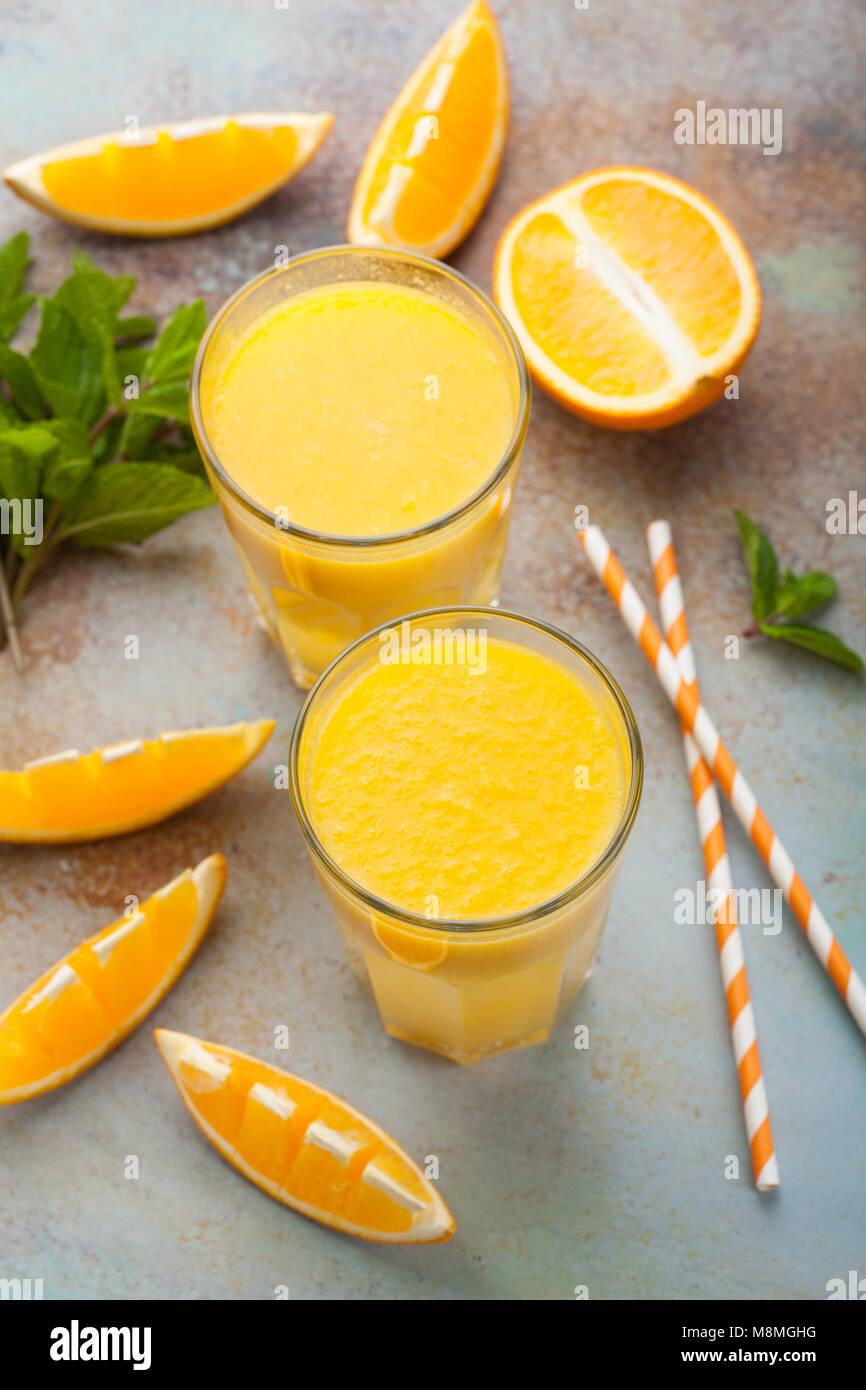 Due bicchieri con spremuta di arancia e menta su un vecchio arrugginito sfondo blu. Vista superiore Immagini Stock