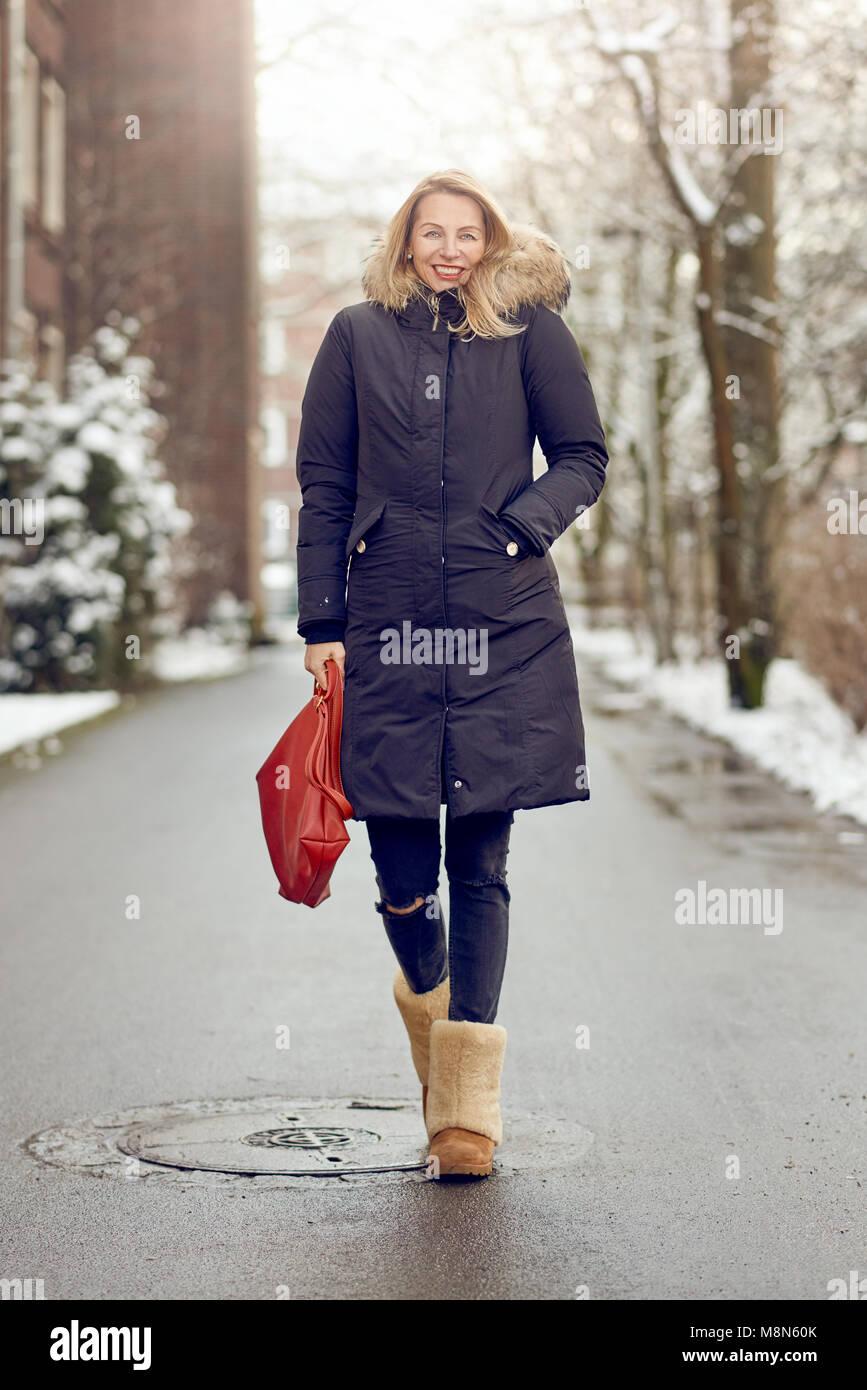 ... bionda in un caldo cappotto invernale e pelosi stivali camminando giù  un freddo strada innevata in inverno di sorridere quando si avvicina al  camer 5d966d9649d