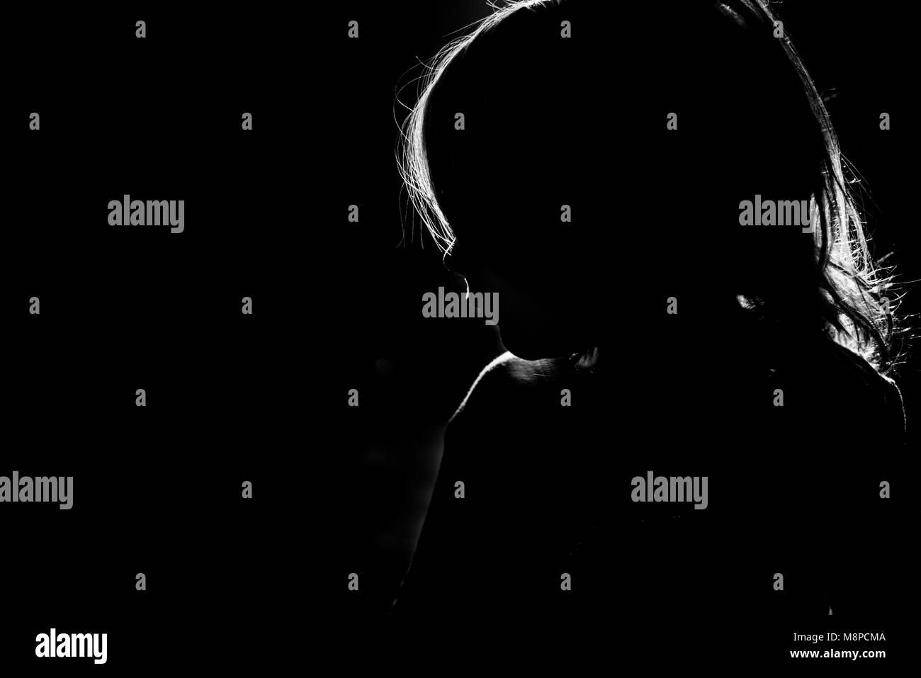 La silhouette di una ragazza giovane con una luce dietro di lei. Immagini Stock