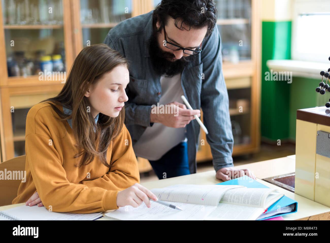 Giovane insegnante aiutando il suo studente in chimica classe. Istruzione, tutoring e incoraggiamento del concetto. Immagini Stock