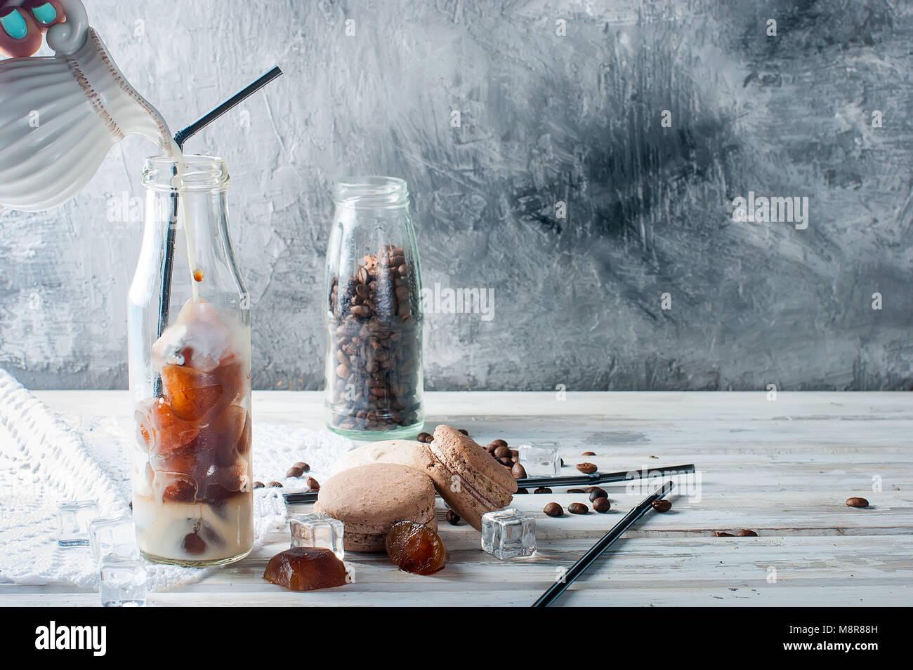 Il caffè di ghiaccio in bottiglia, amaretti,, pezzi di cioccolato e chicchi di caffè al buio su un tavolo Immagini Stock