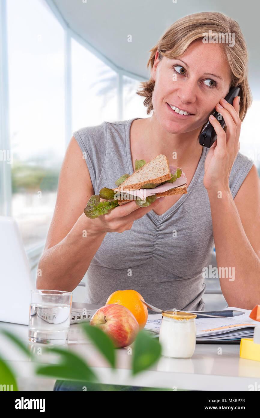 Giovane donna di affari di mangiare insalata in un grande ufficio finestre, avente un sano pranzo al posto di lavoro Immagini Stock