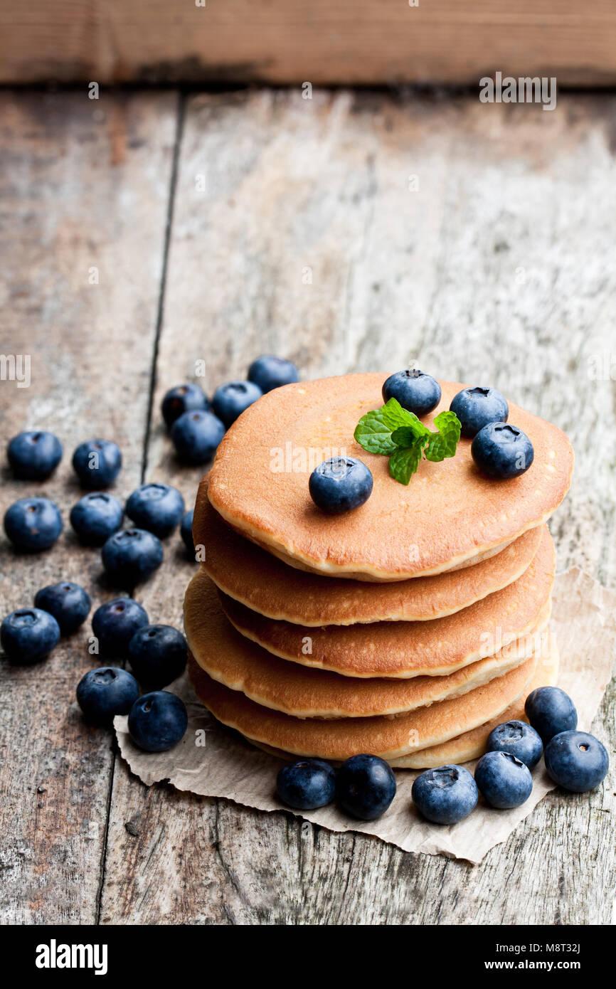 Pila di scotch pancake con mirtilli freschi sul tavolo di legno Immagini Stock