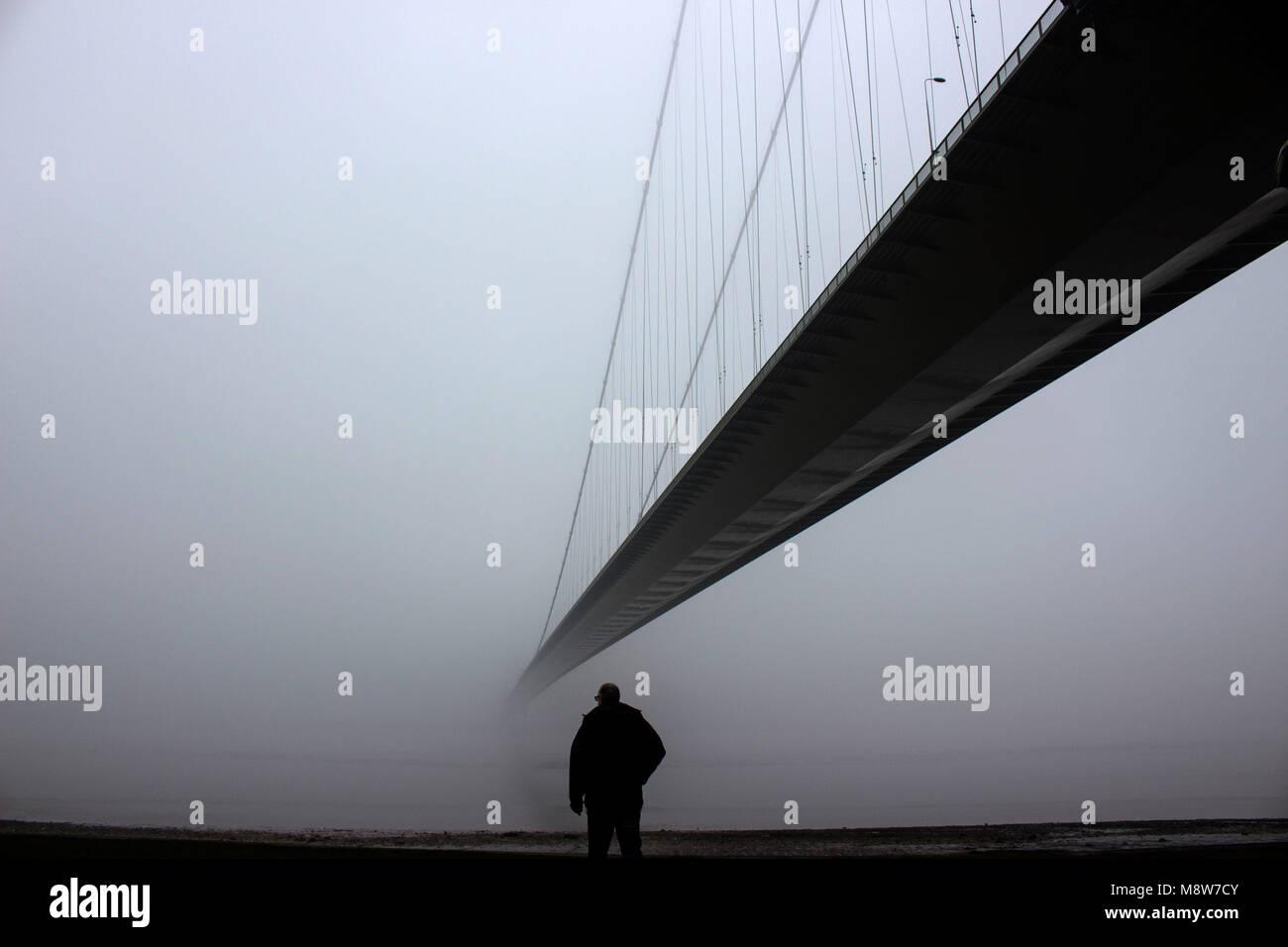 Humber Bridge con la nebbia, un uomo che guarda al fiume, nello Yorkshire, Inghilterra, Regno Unito Immagini Stock