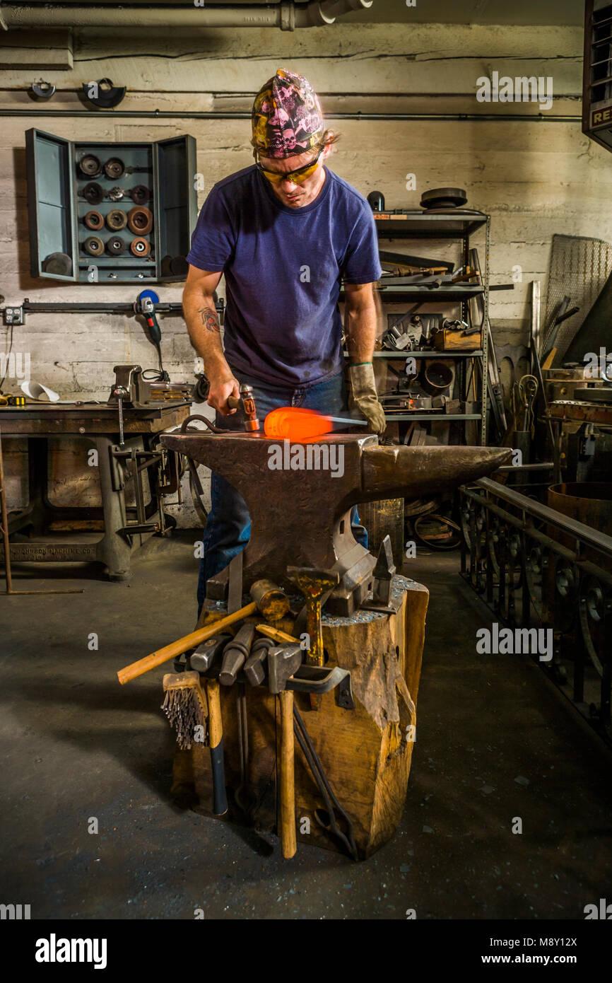 Un uomo che lavora in una officina di fabbro con martello e l'incudine. Immagini Stock