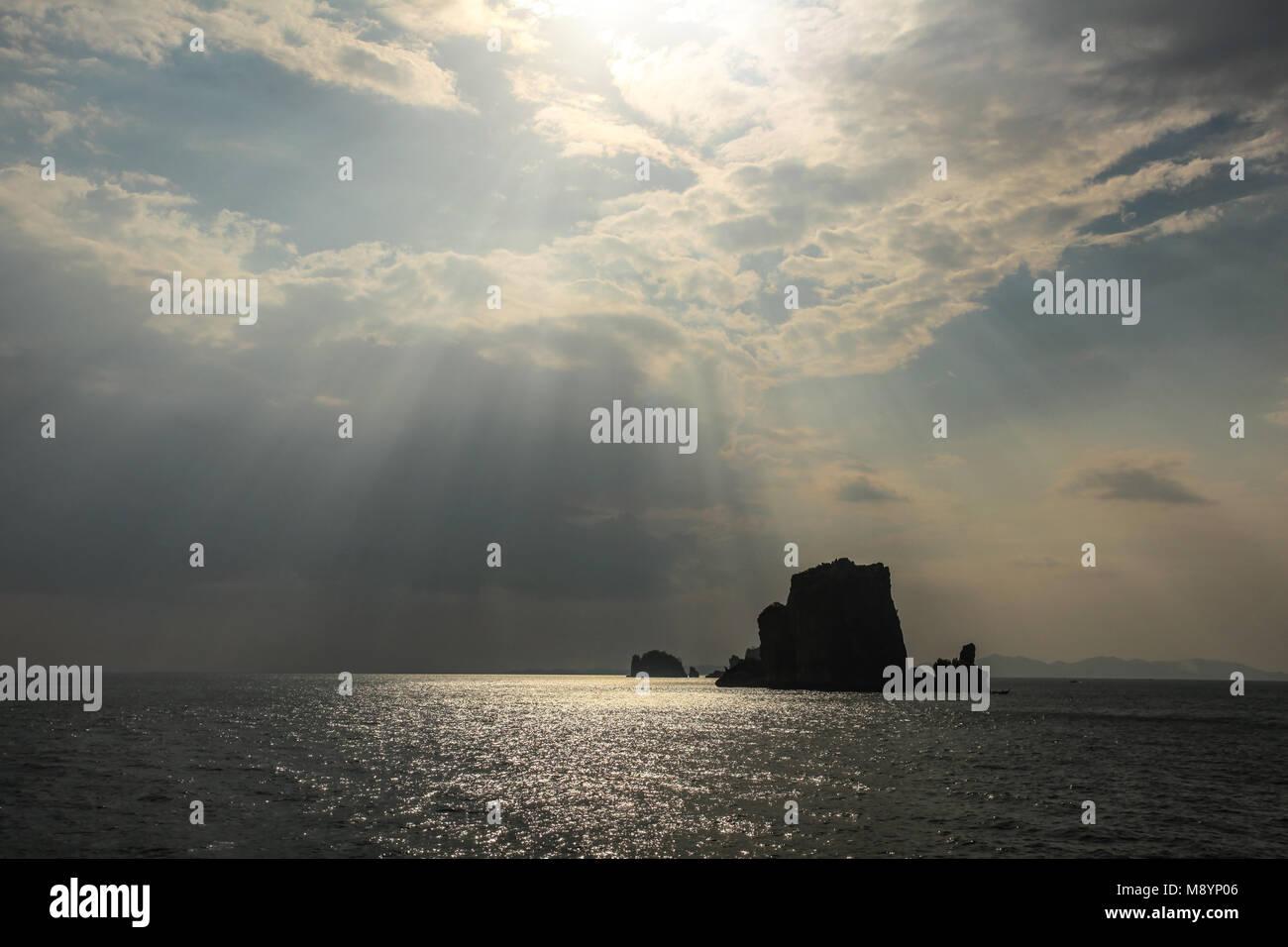 Raggi di sole che splende su piccola isola deserta nel mare delle Andamane vicino a Phi Phi, mostrando solo silhouette Immagini Stock
