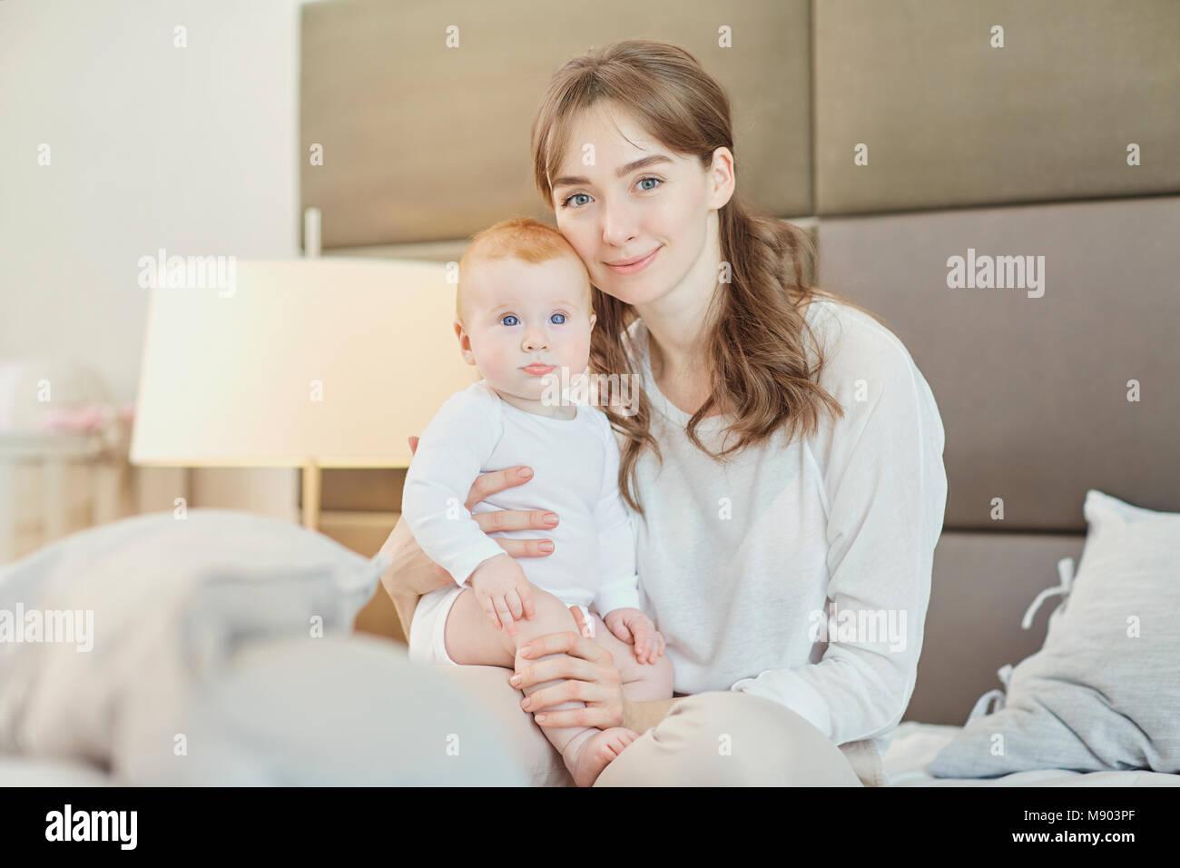 Ritratto madre gioca con i bambini sul letto. Immagini Stock