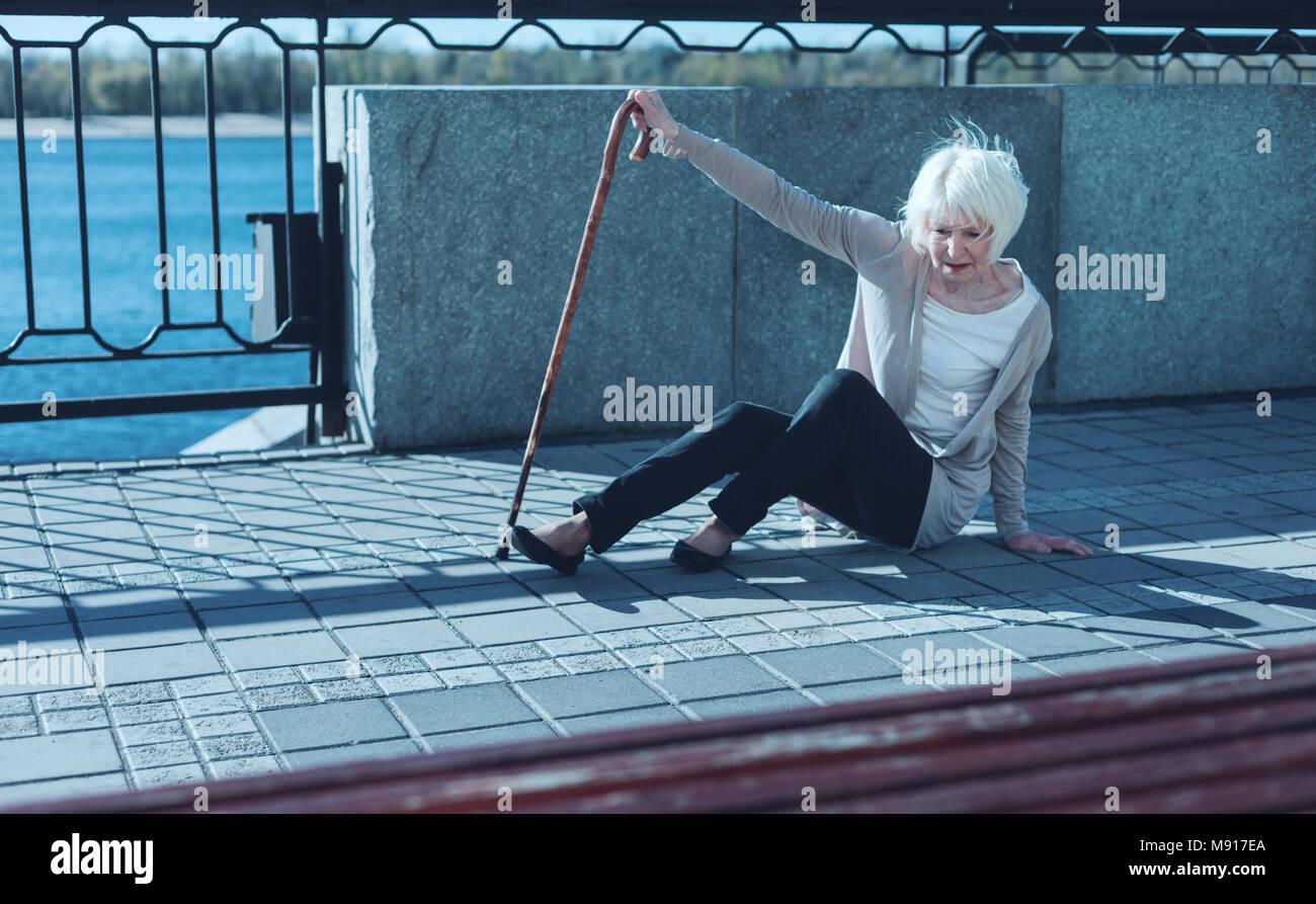 Gli anziani poveri signora cadendo all'aperto Foto Stock