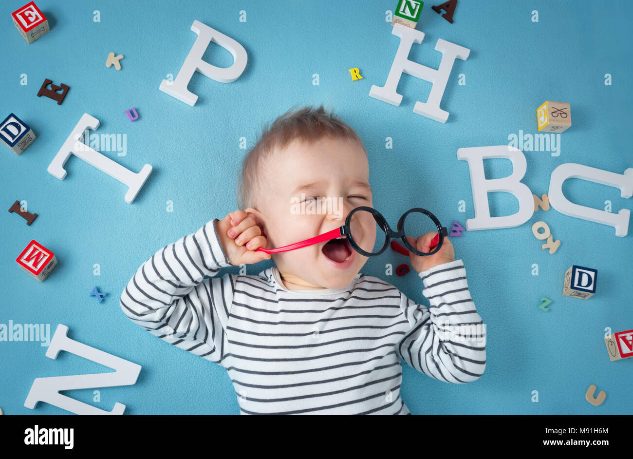 Un anno di età bambino giacente con occhiali e lettere Immagini Stock