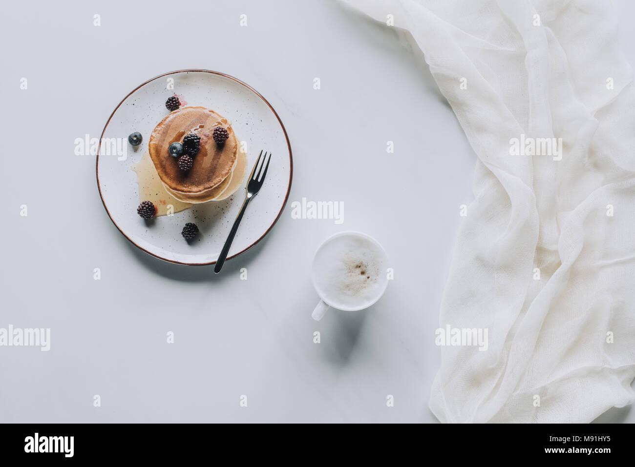 Vista superiore della tazza di cappuccino e dolci gustosi pancake con frutti di bosco e miele su grigio Immagini Stock