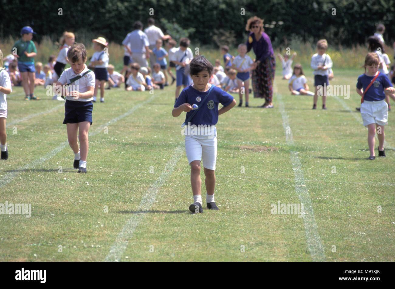 La scuola primaria chldren competere in uovo e cucchiaio gara durante la giornata dello sport, England, Regno Unito Immagini Stock