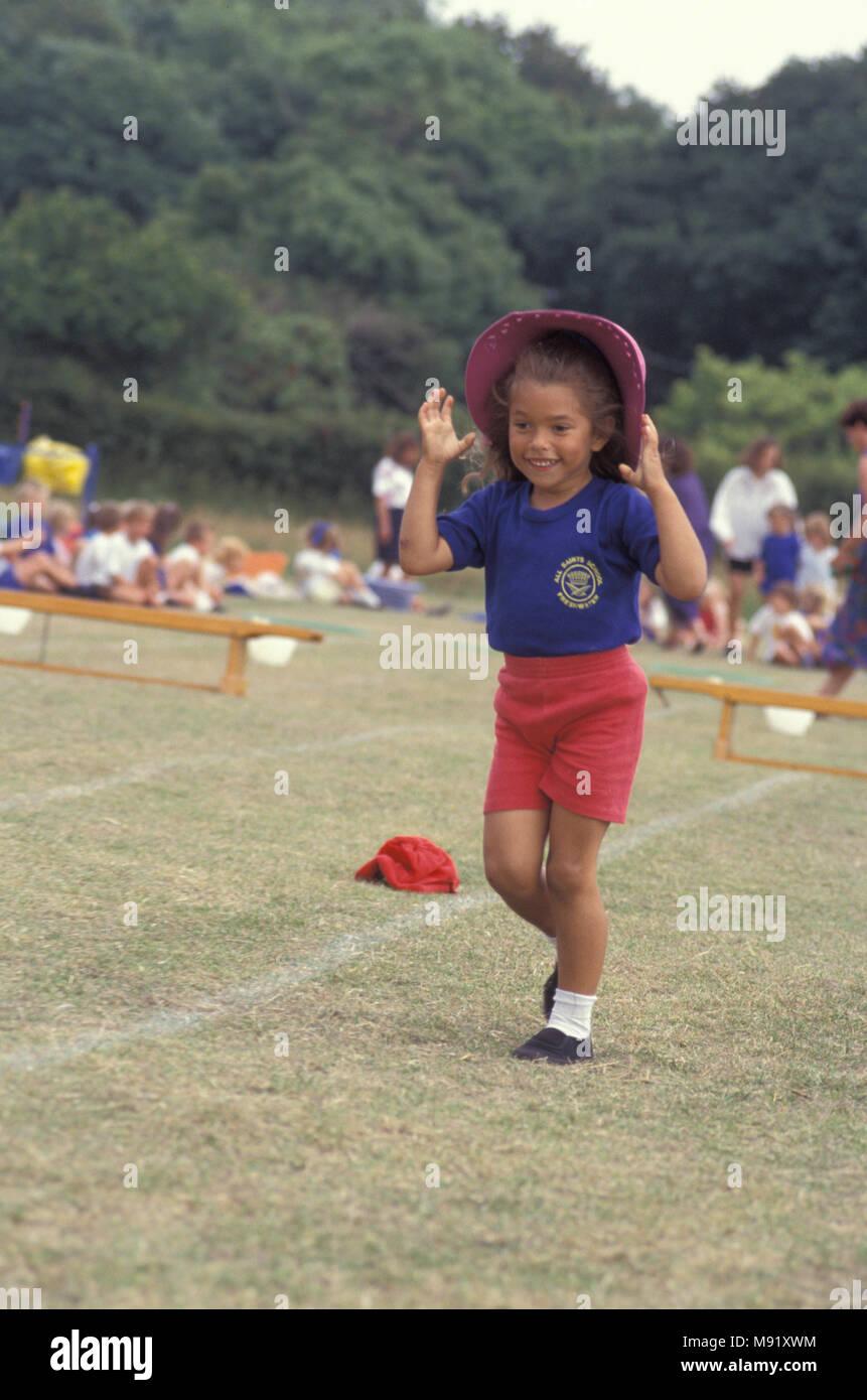 Bambina in competizione in giornata di sport gioco cercando di mantenere hat su, England, Regno Unito Immagini Stock
