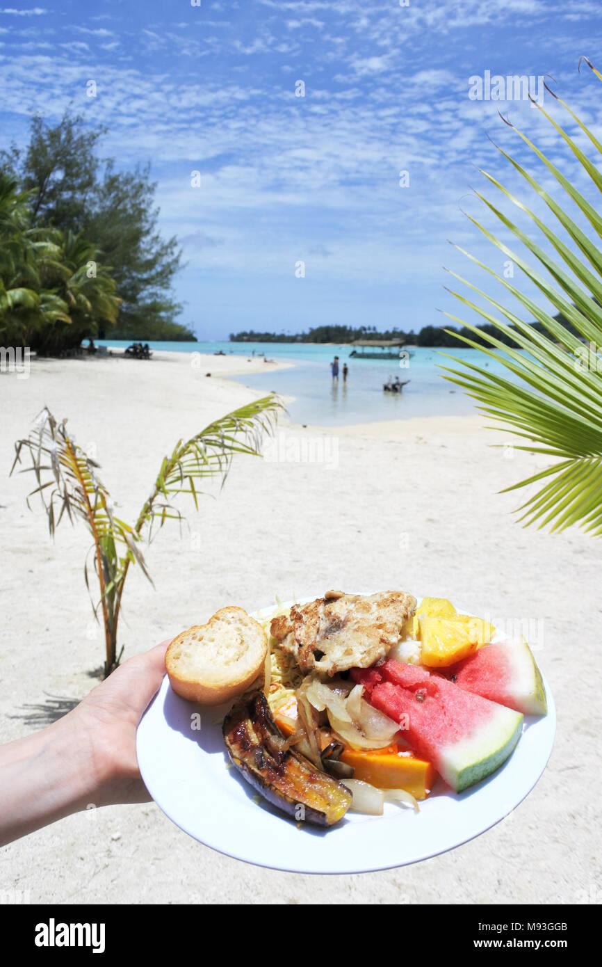 Donna trasporto a mano tradizionale cibo tropicale di grigliate di pesce, frutta e verdura pietanza servita su isolotto di Muri lagoon Rarotonga Isole Cook. Copia sp Immagini Stock