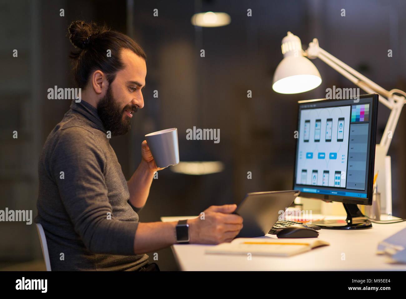 Uomo creativo con il computer lavora fino a tardi in ufficio Immagini Stock