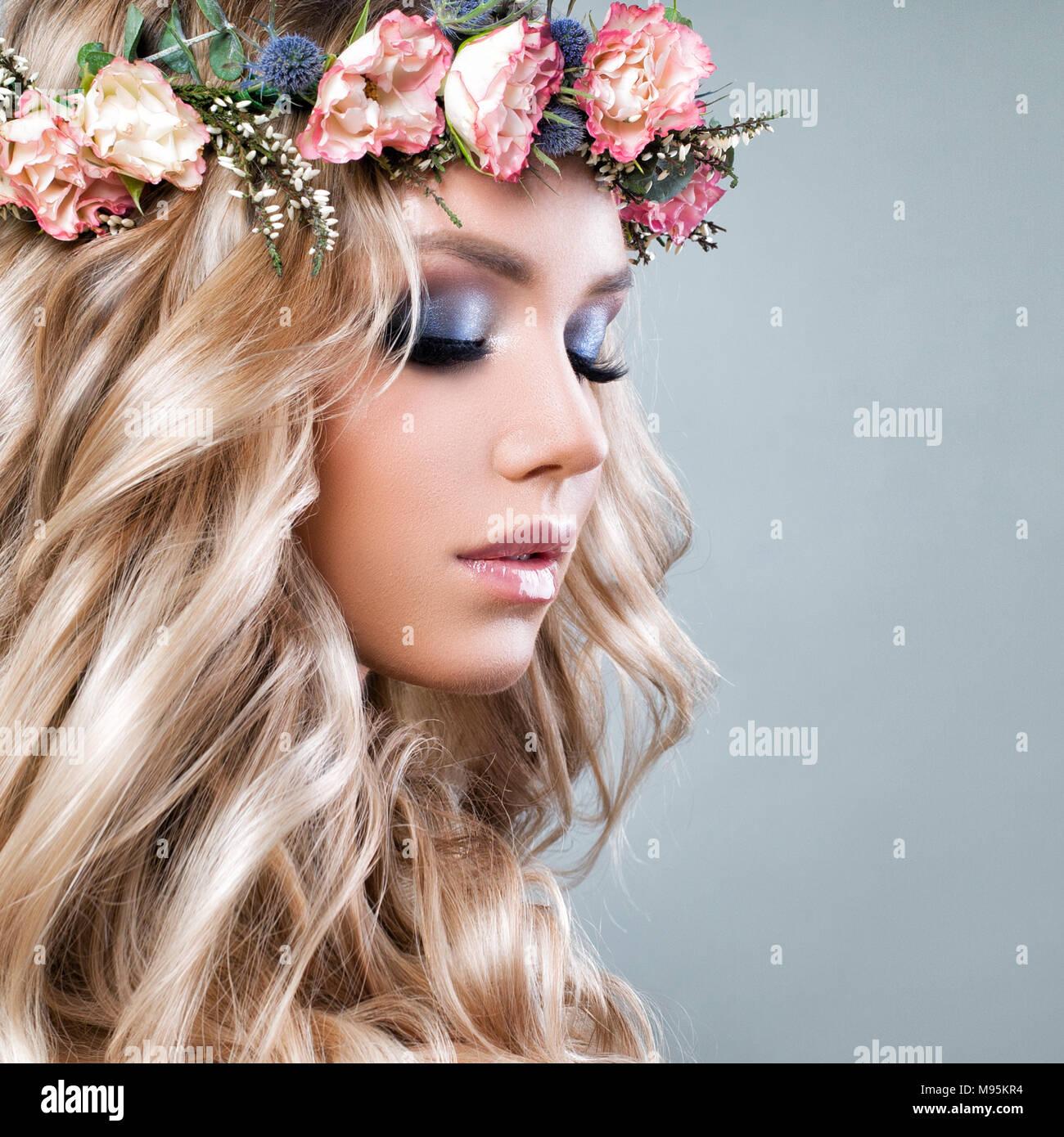 Bella donna estate con fiori di colore rosa. Bionda bellezza. Lunga permed  capelli ricci e il trucco di moda. Bellezza ragazza con fiori acconciatura 9f4909ee89aa