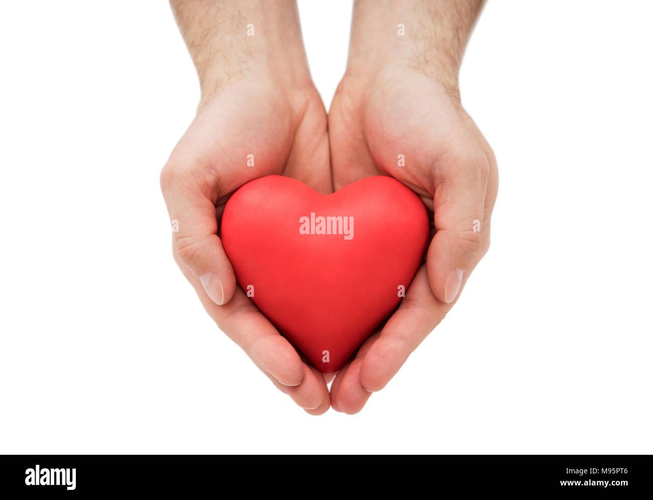Cuore rosso nelle mani dell'uomo. Assicurazione sanitaria o concetto di amore Foto Stock