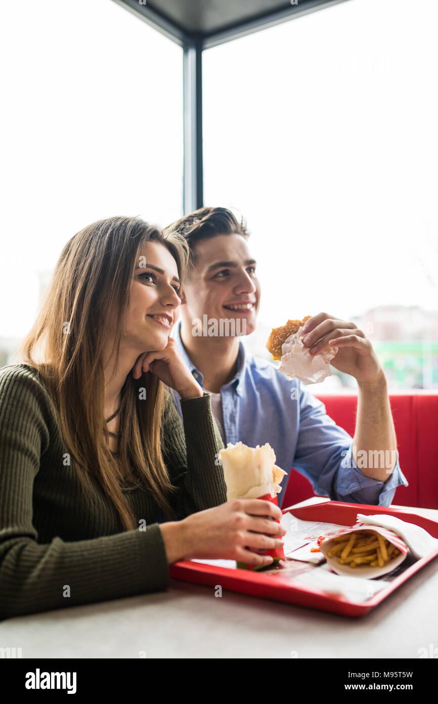 Un felice donna sorridente e un uomo bello stanno godendo i loro deliziosi e gustosi hamburger Immagini Stock