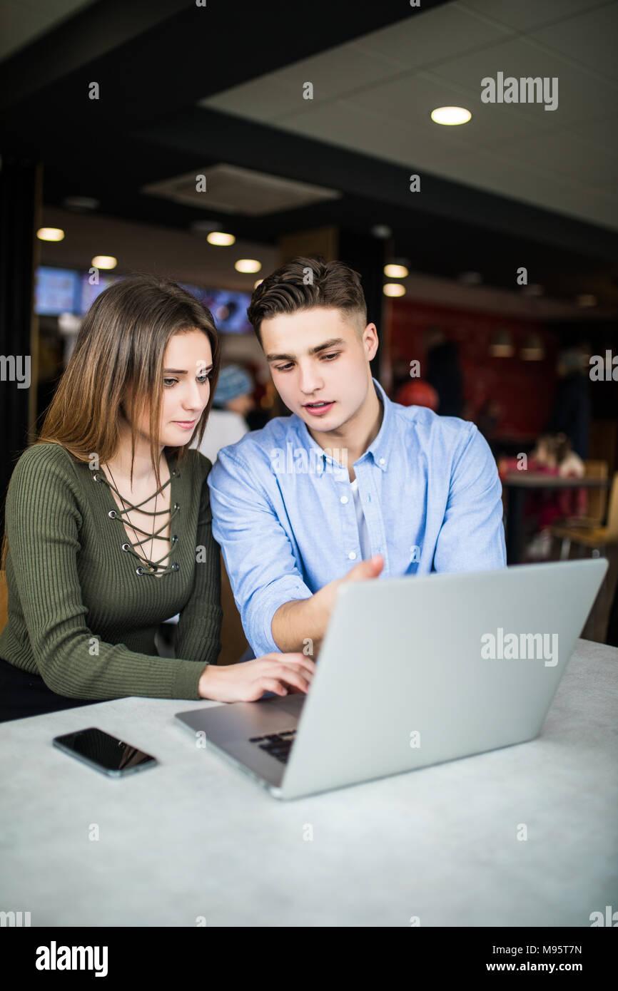 Coppia felice è utilizzando un computer portatile, a bere caffè e sorridenti mentre è seduto presso il cafe Immagini Stock