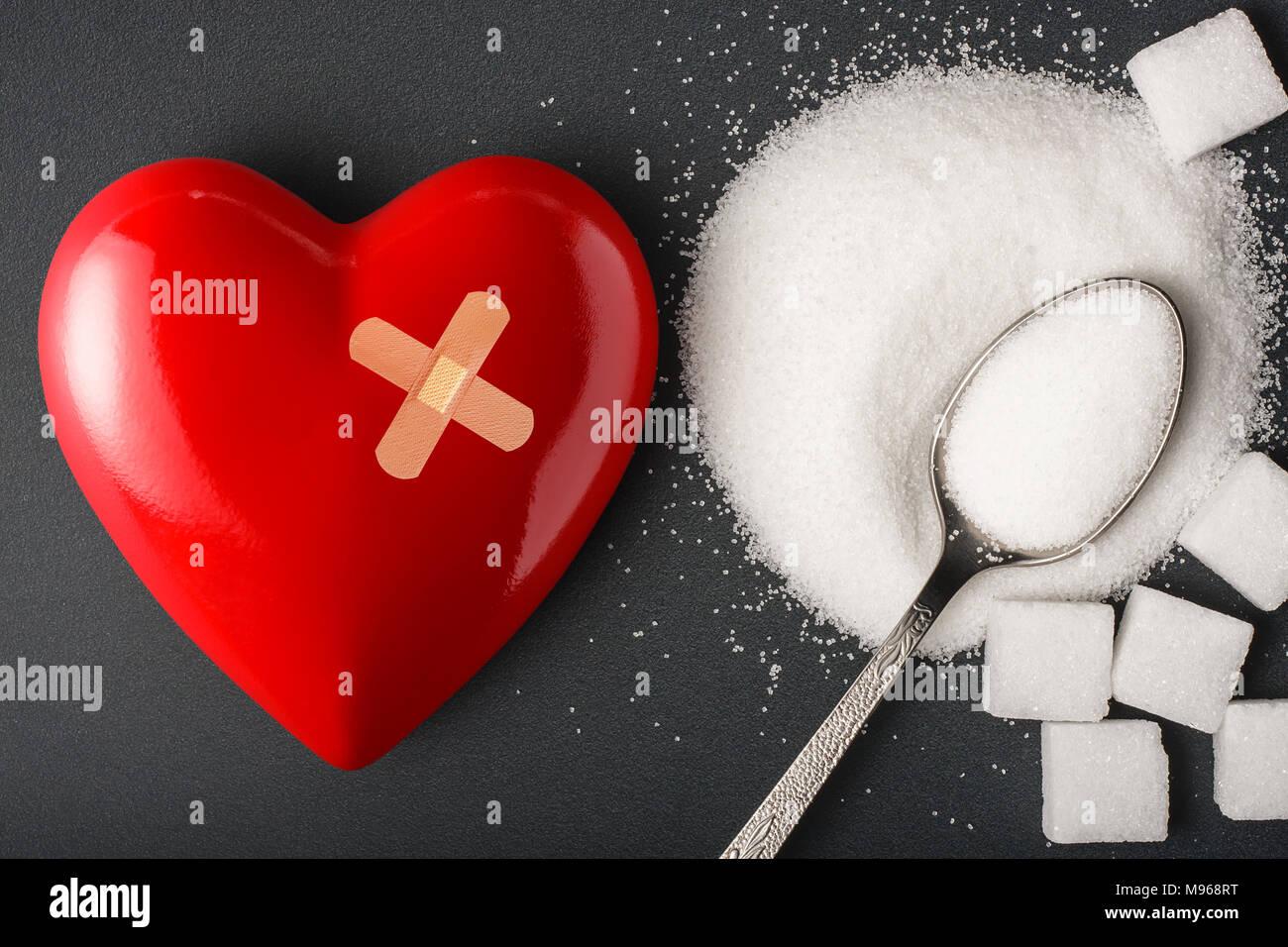 Cibo malsano concetto - zucchero. Cucchiaio con lo zucchero e il cuore con bendaggio Immagini Stock