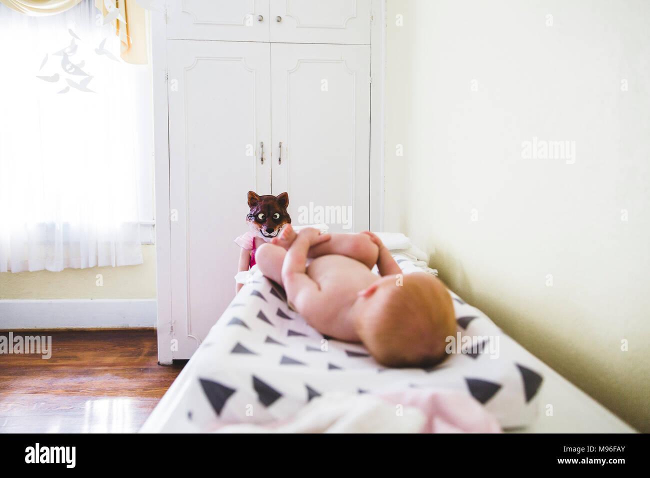Baby posa sul fasciatoio con maschera in background Immagini Stock