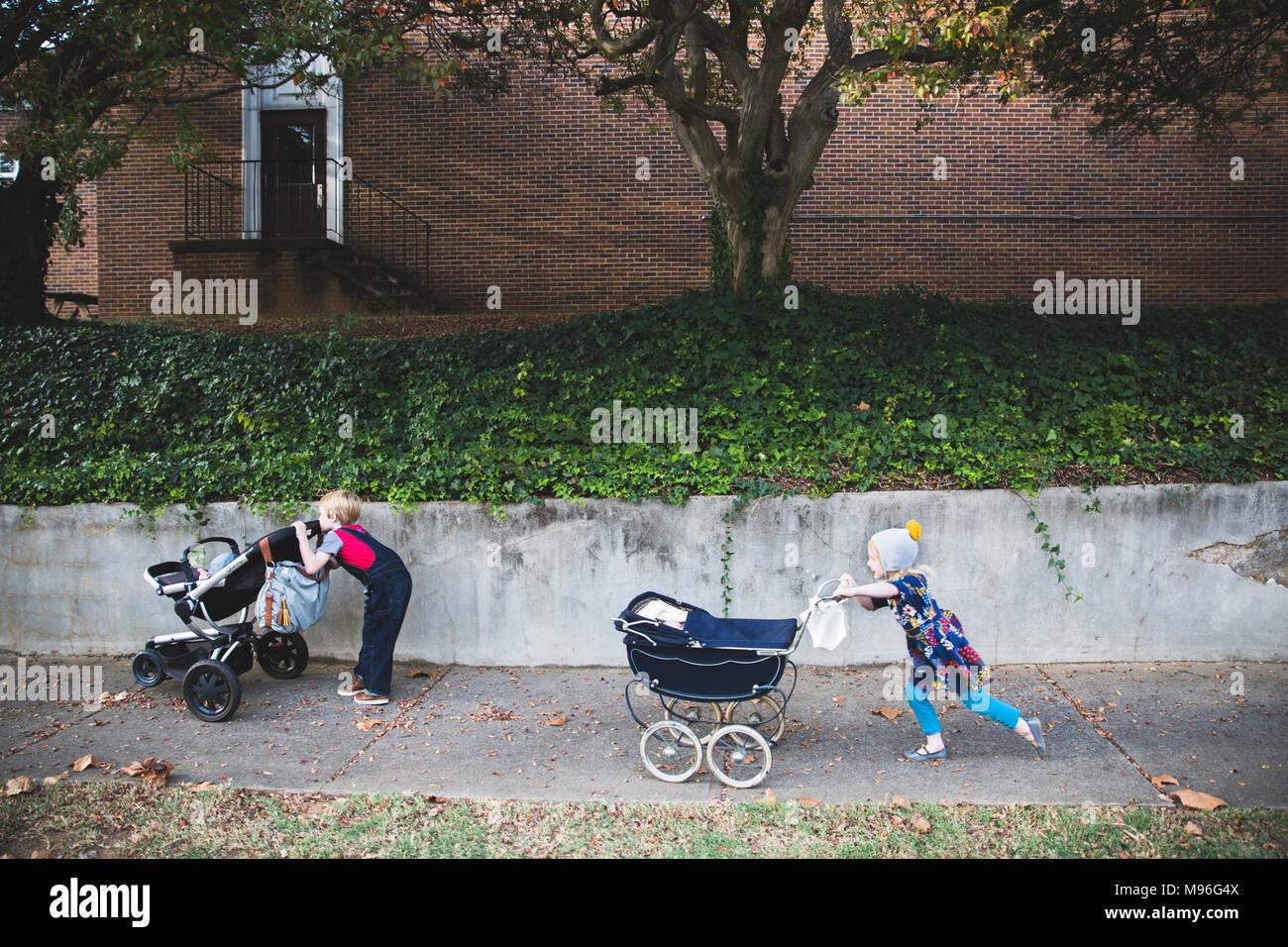 Bambini spingendo carrozzine lungo la strada Immagini Stock