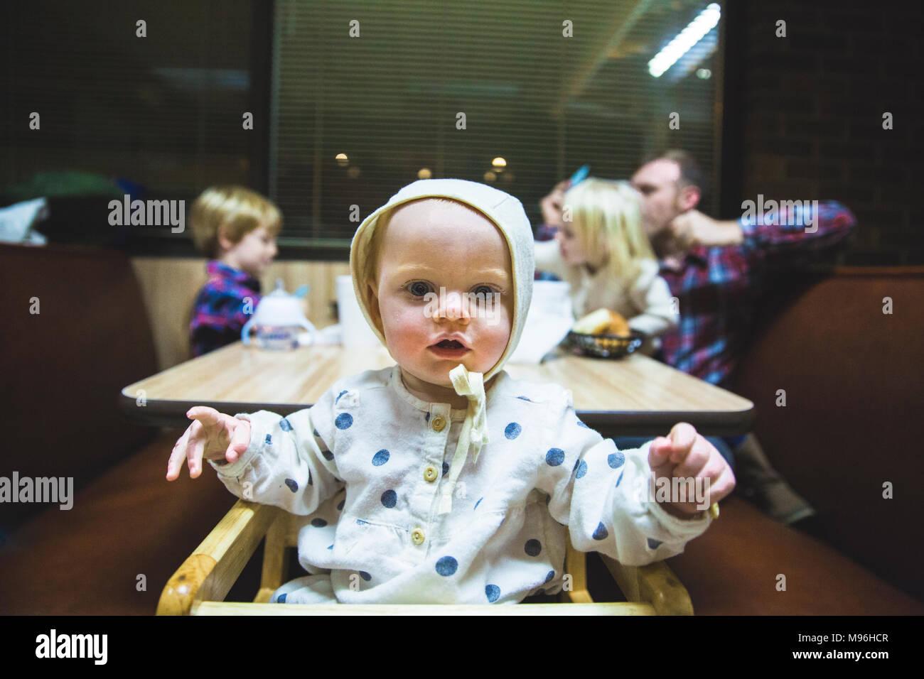 Baby guardando la fotocamera con la famiglia sat in diner booth dietro Immagini Stock