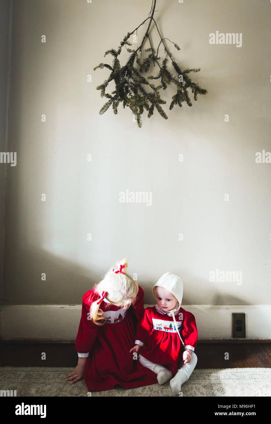 La ragazza e il bambino seduto sul pavimento al di sotto del verde Immagini Stock
