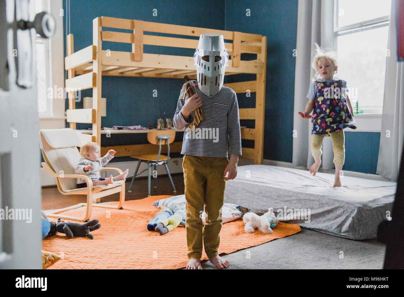 Ragazzo con cavaliere del casco in piedi in camera da letto Immagini Stock