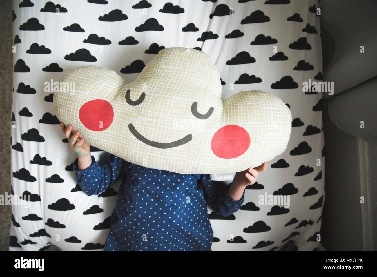 Ragazza la posa sul letto con cuscino cloud oltre il suo volto Foto Stock