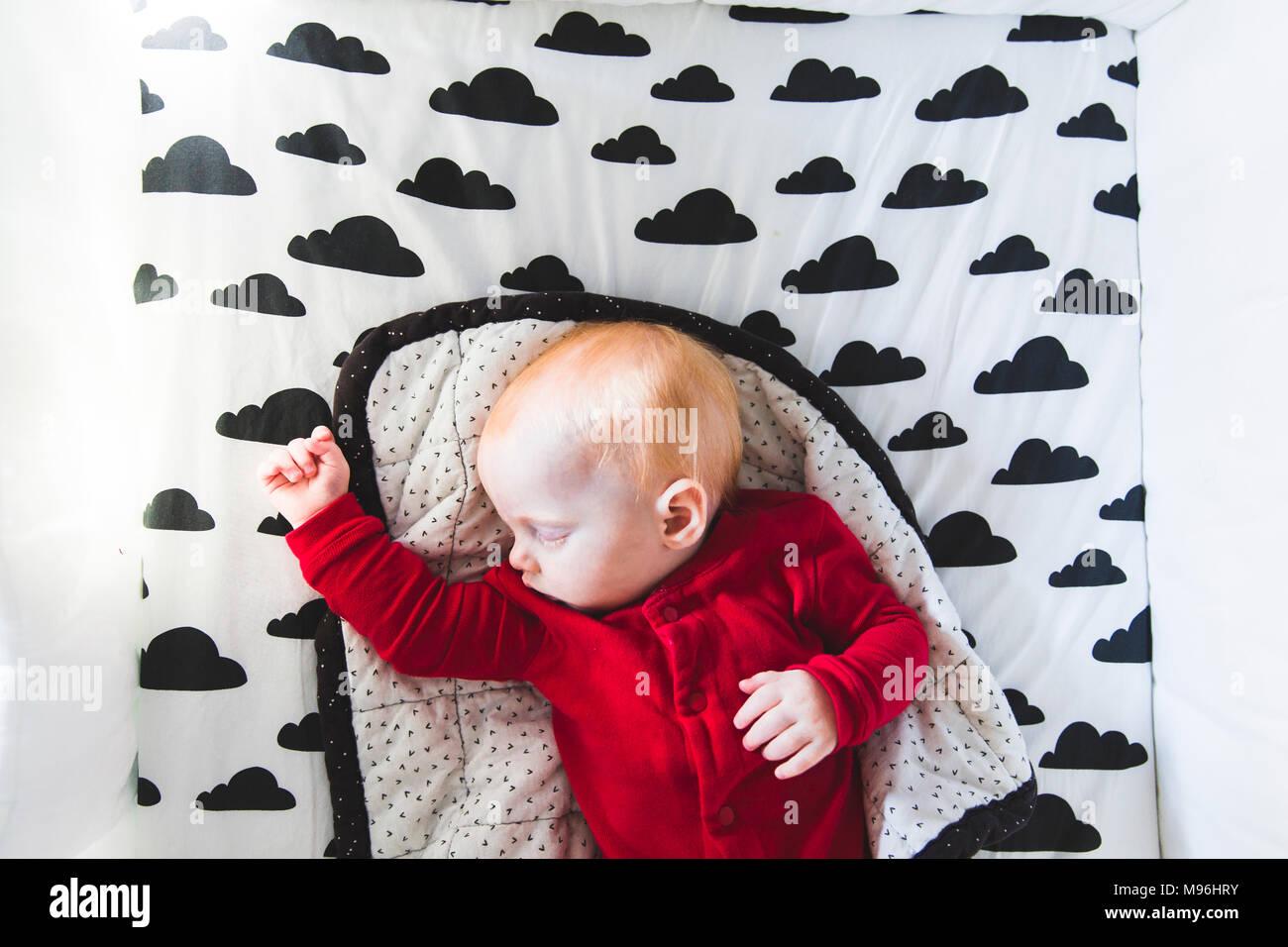 Il bambino che dorme sul letto con la decalcomania del cloud Immagini Stock