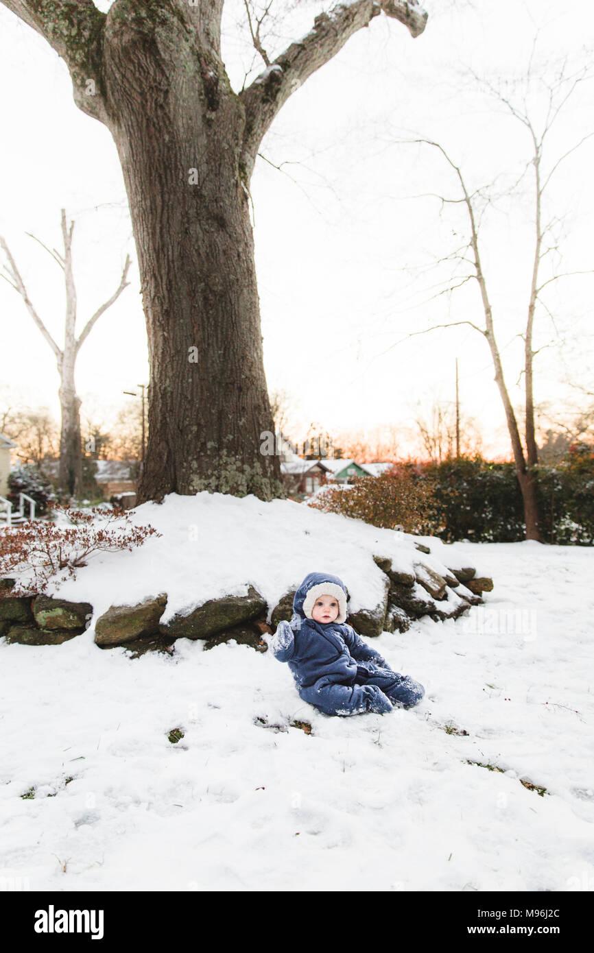 Ragazza seduta nella neve con giacca blu su Immagini Stock