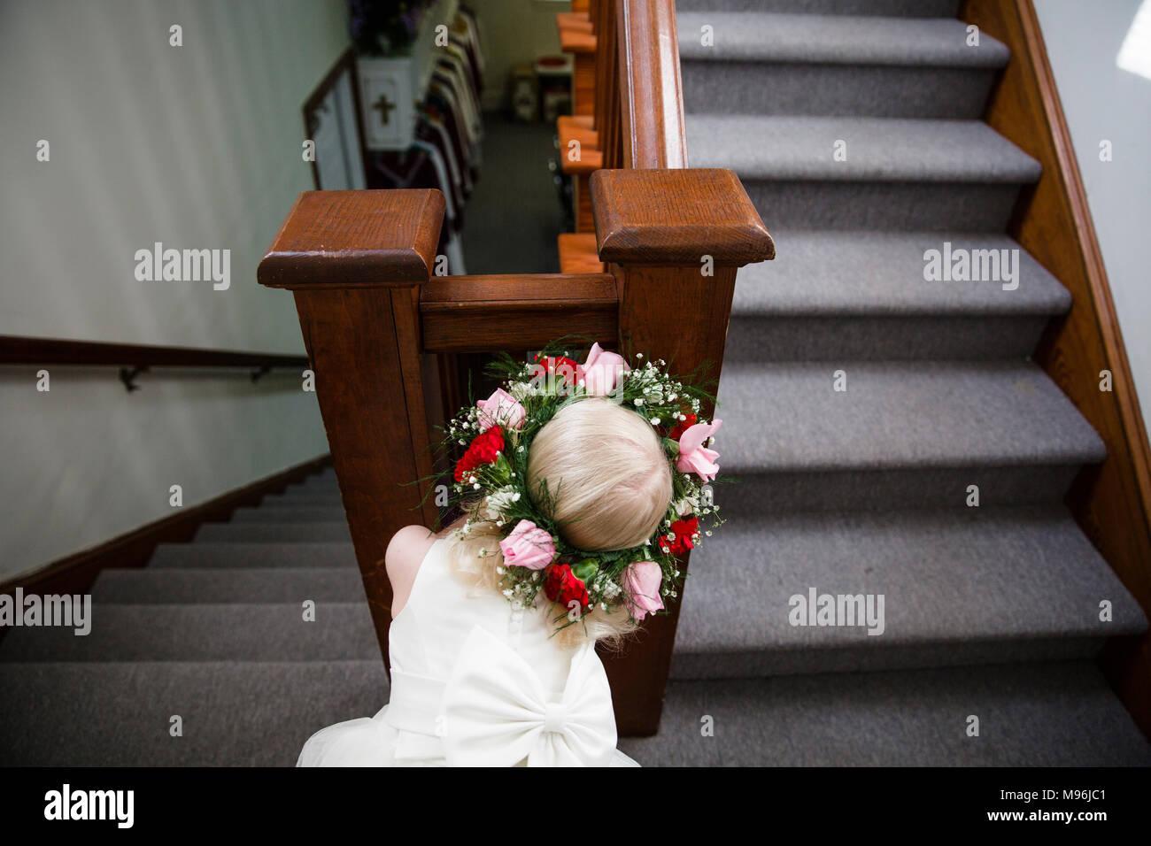 Ragazza in abito bianco cerca attraverso ringhiere per scale Immagini Stock
