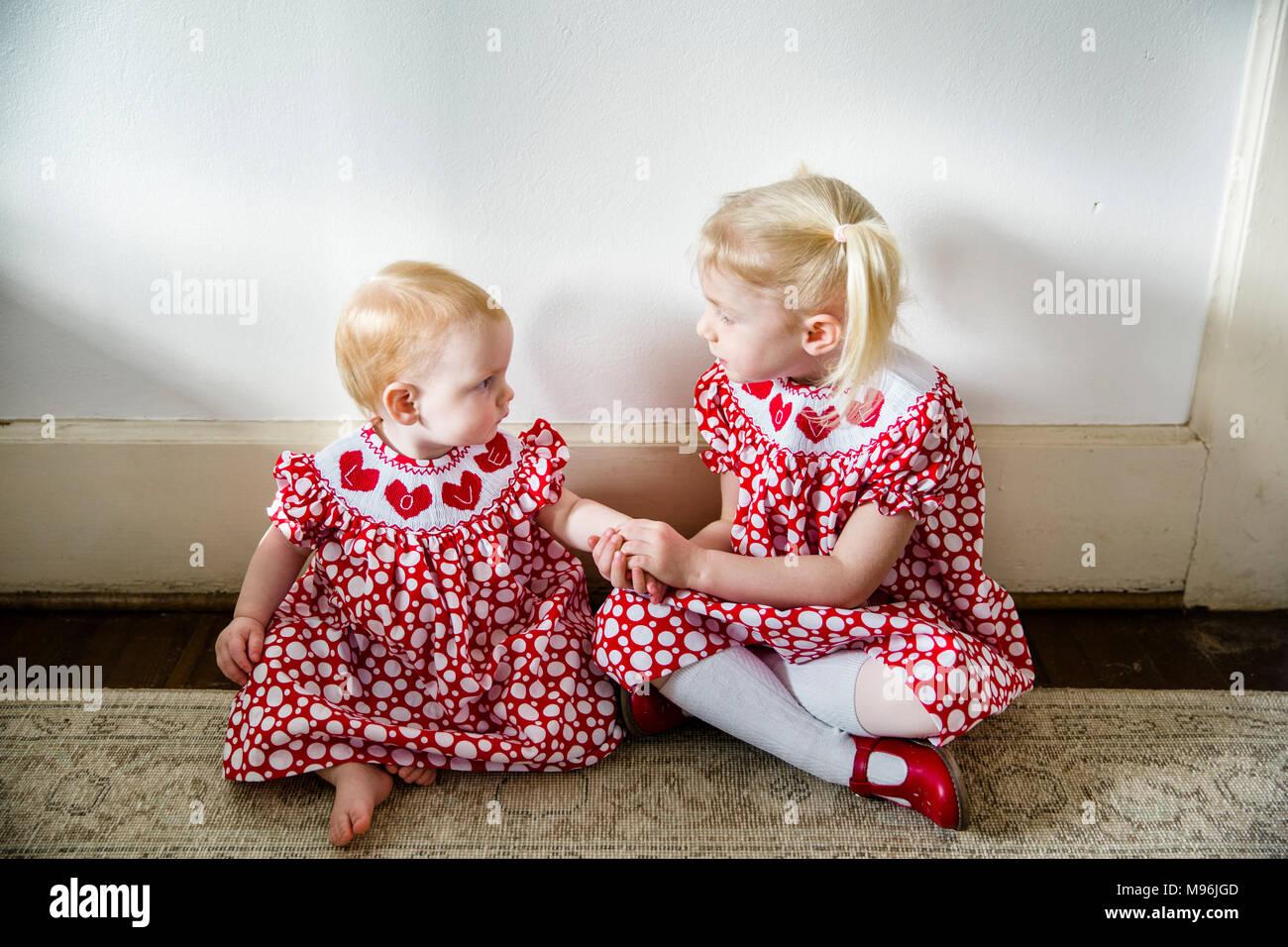 Bambino e bambina guardando ogni altro nella stessa veste rossa Immagini Stock