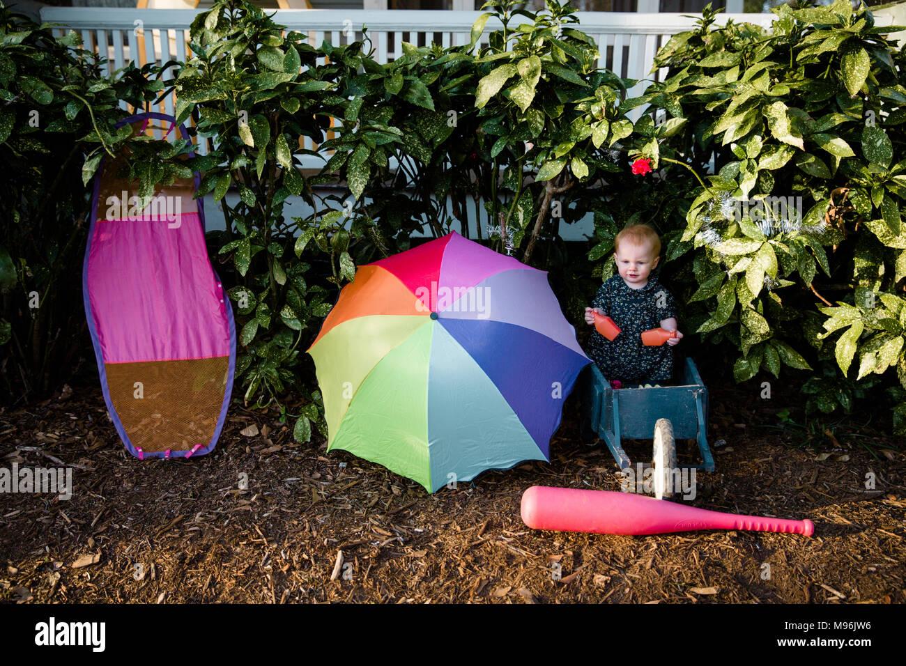 Ragazza seduta accanto a ombrello luminoso Immagini Stock