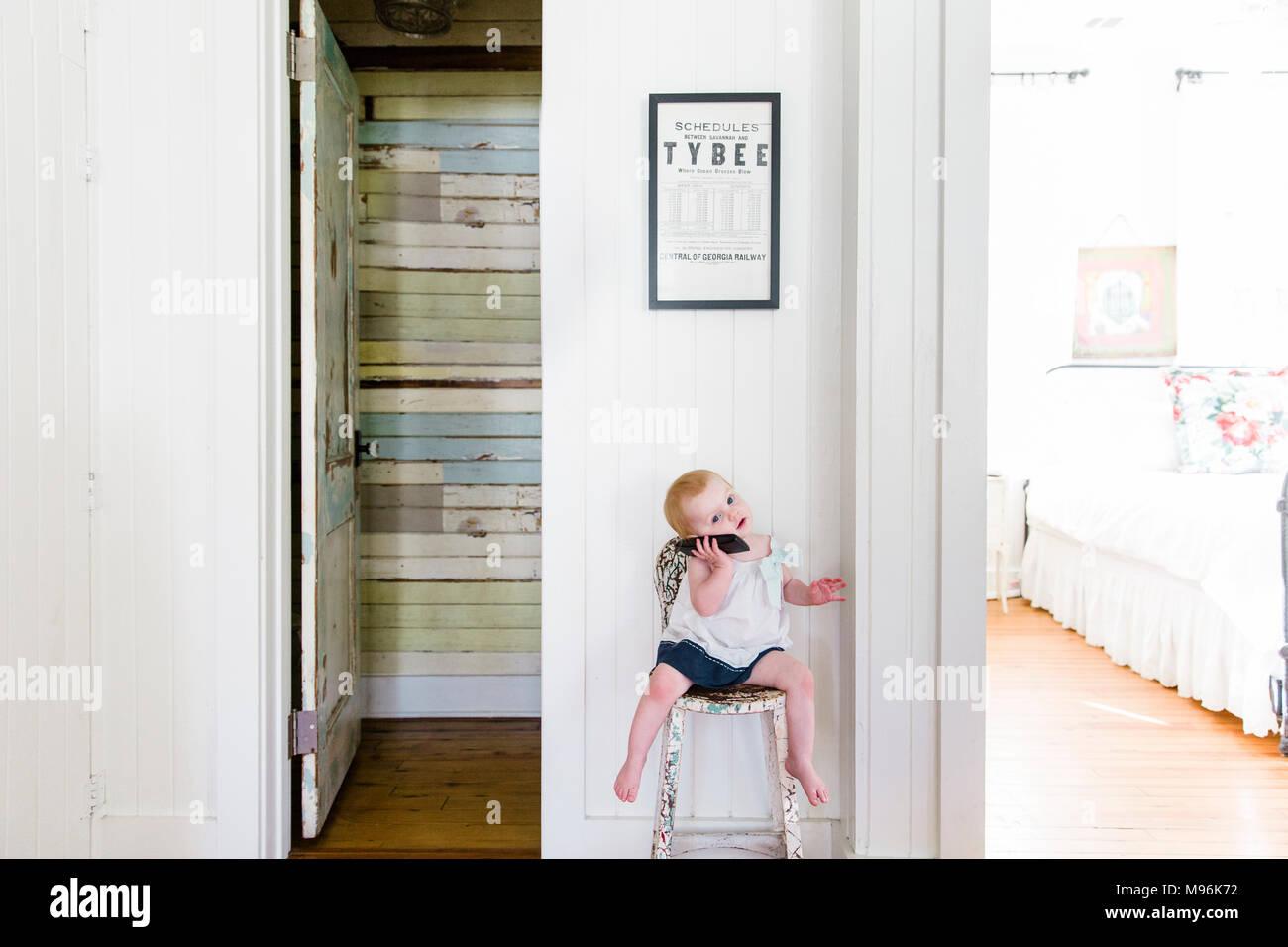 Baby su telefono seduti su una sedia Immagini Stock