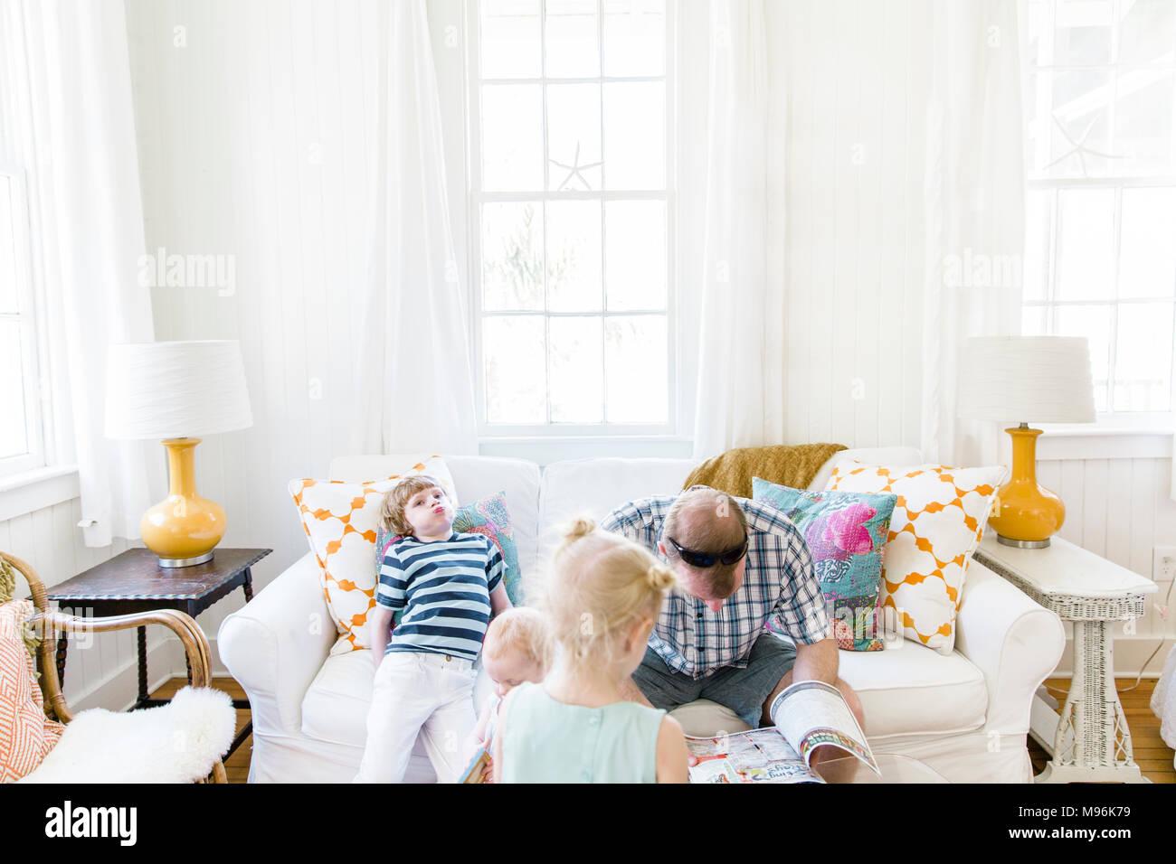 L'uomo la lettura sul divano con bambini intorno a lui Immagini Stock
