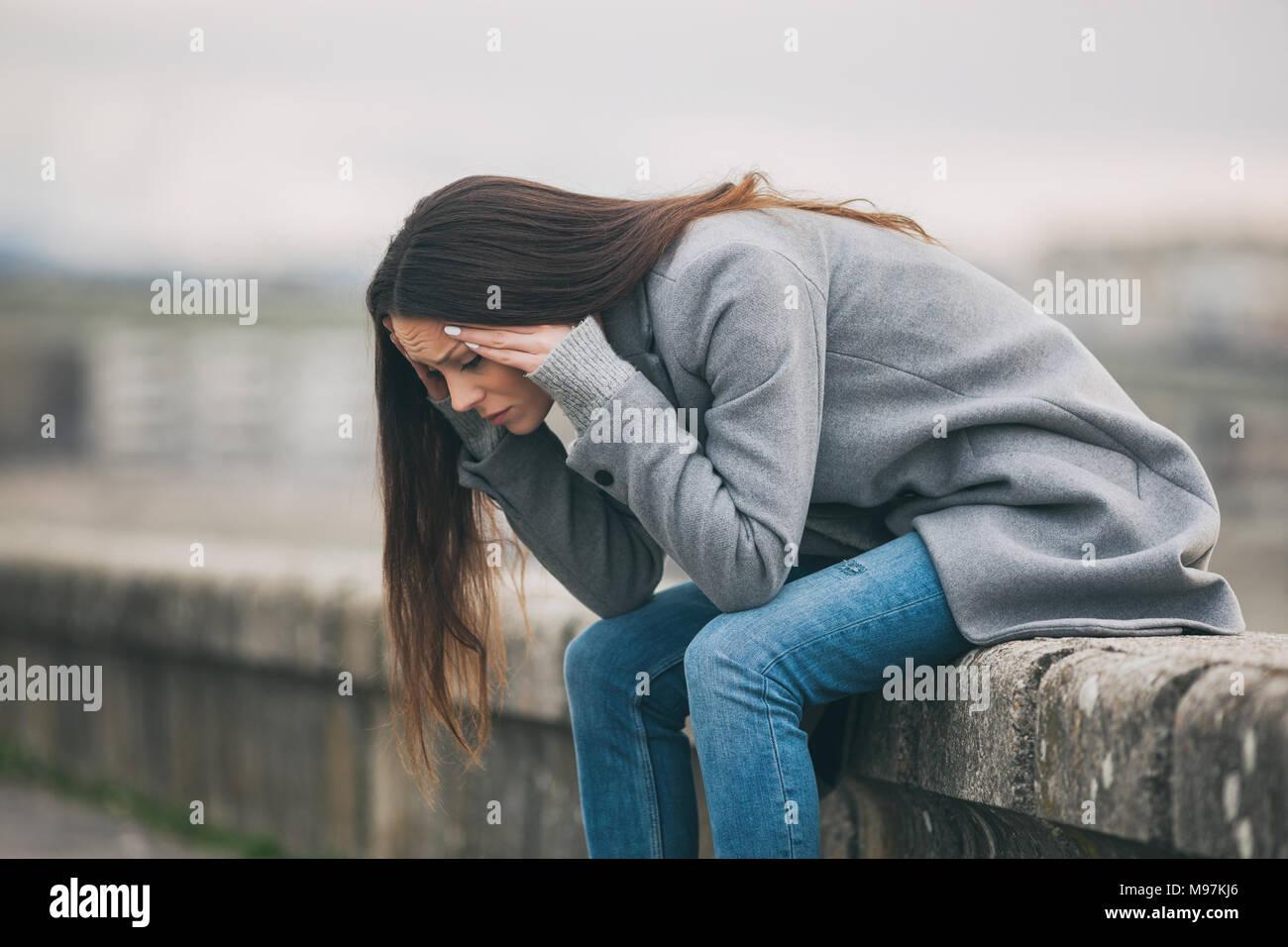 Giovani solitari e premuto la donna è seduta nel dolore. Immagini Stock