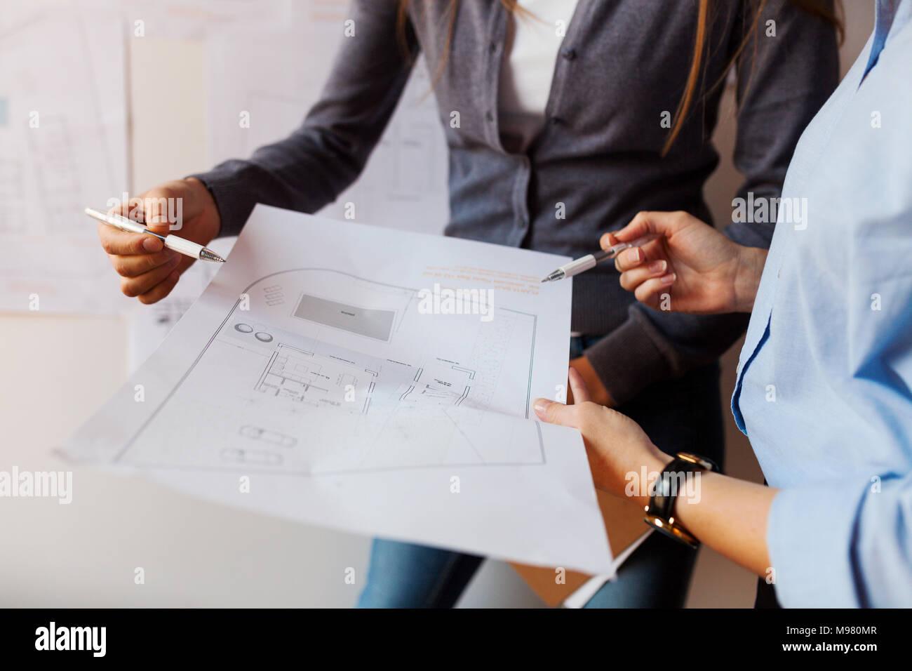 Femmina di architetti che lavorano su un progetto, guardando il blueprint Immagini Stock