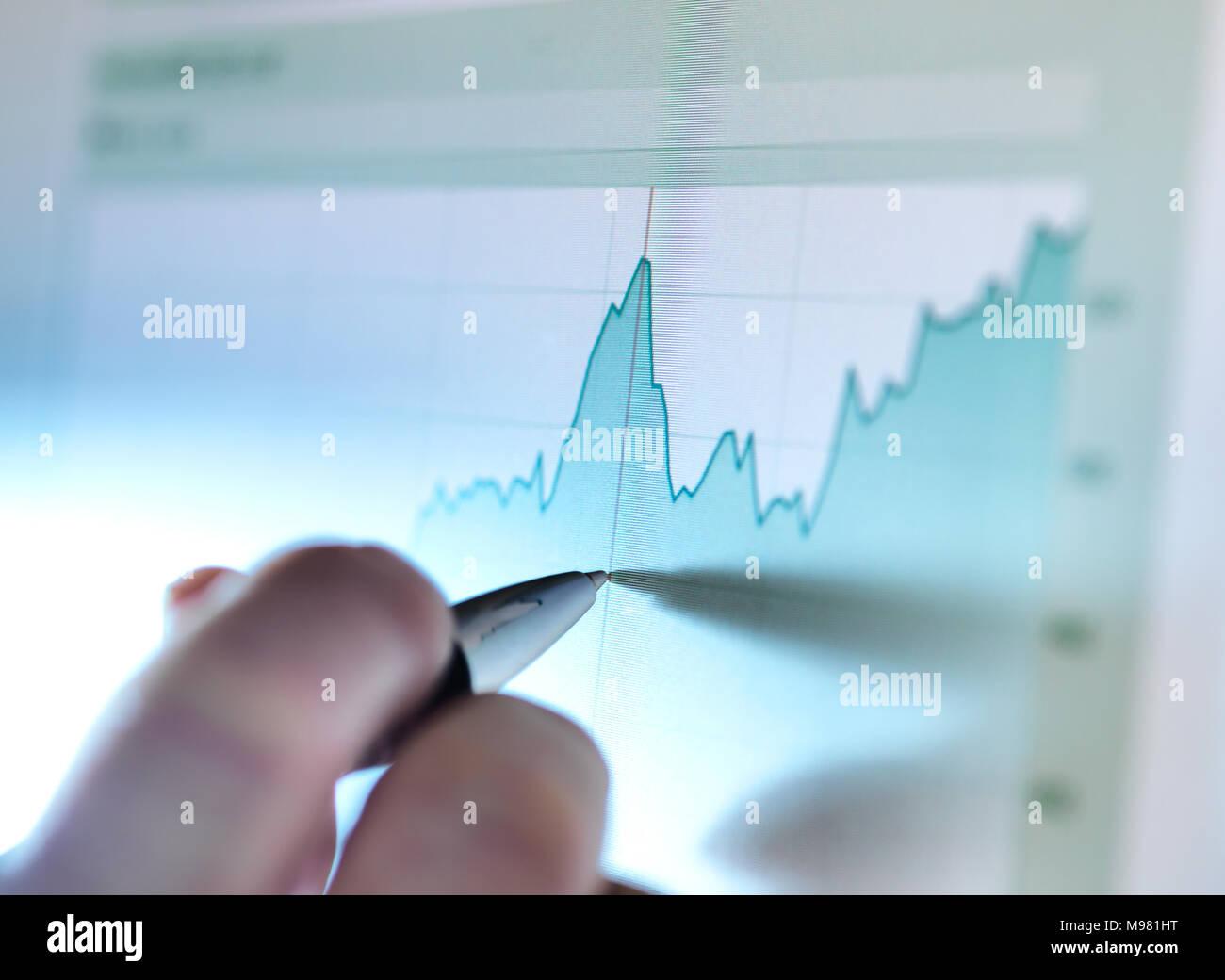 La mano di uno stock broker analizzare linea grafico sullo schermo del computer Immagini Stock