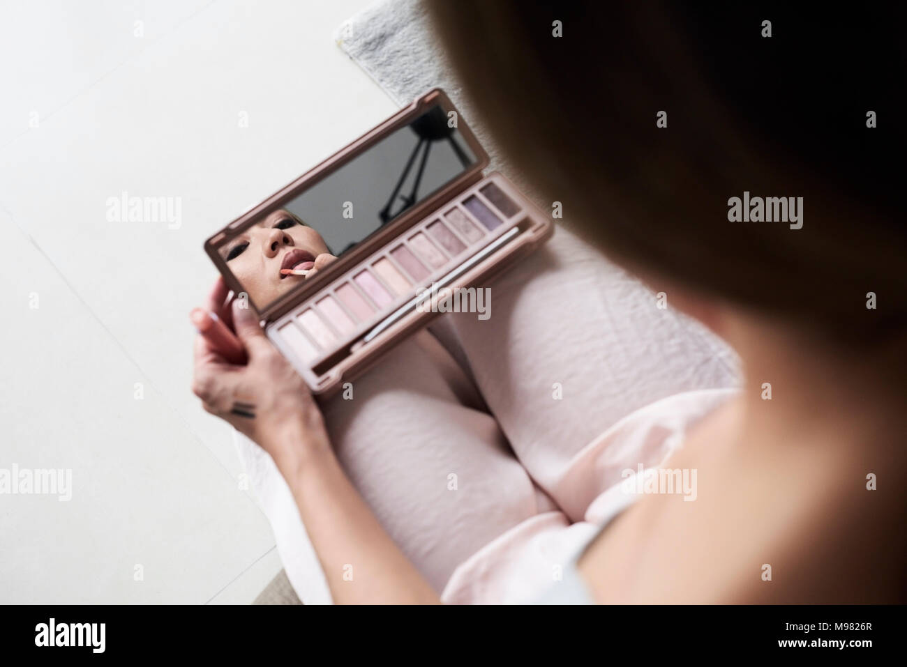 Donna con specchio a mano il rossetto Immagini Stock