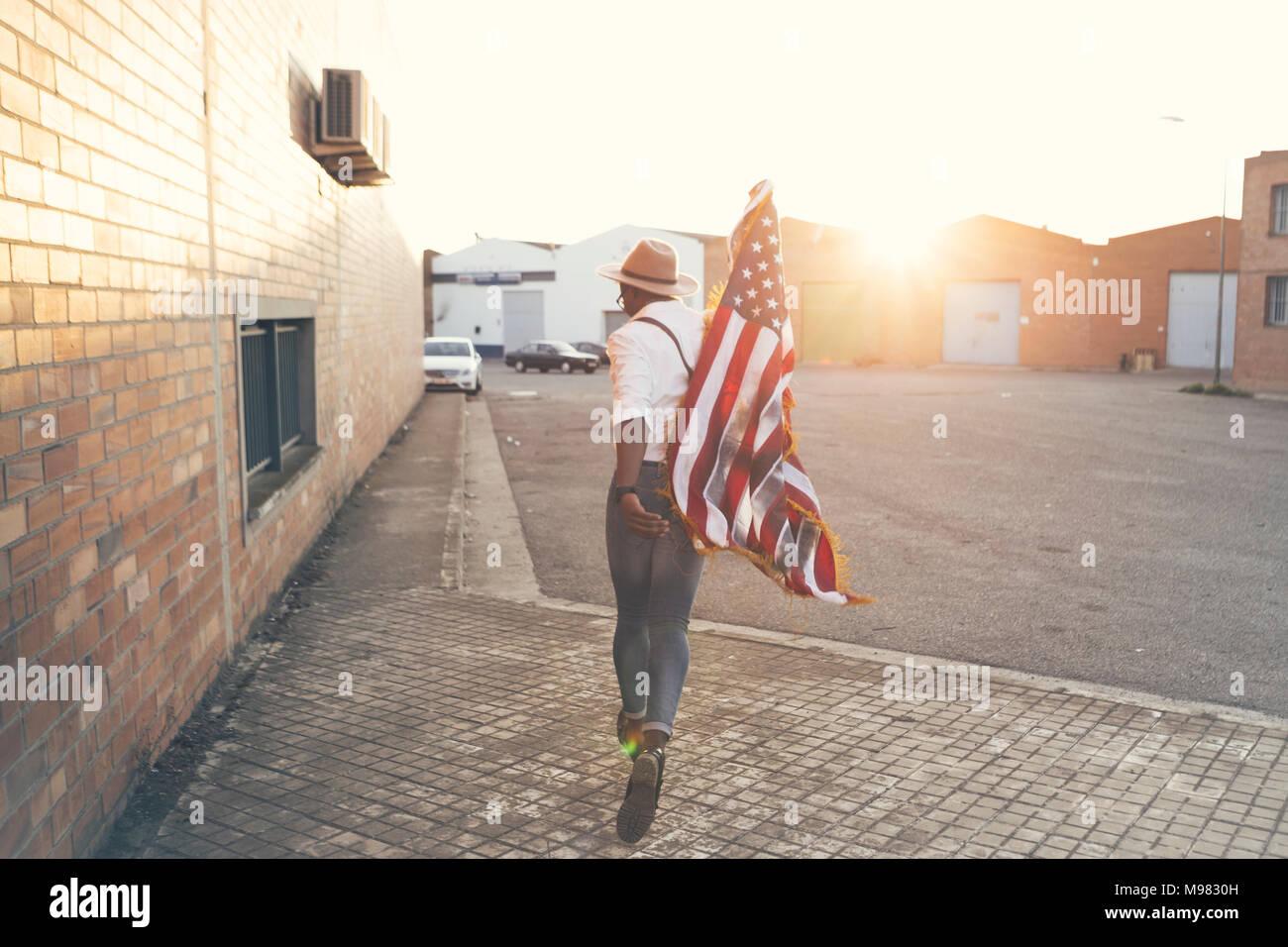 Vista posteriore del giovane uomo che corre con bandiera americana a retroilluminazione Immagini Stock