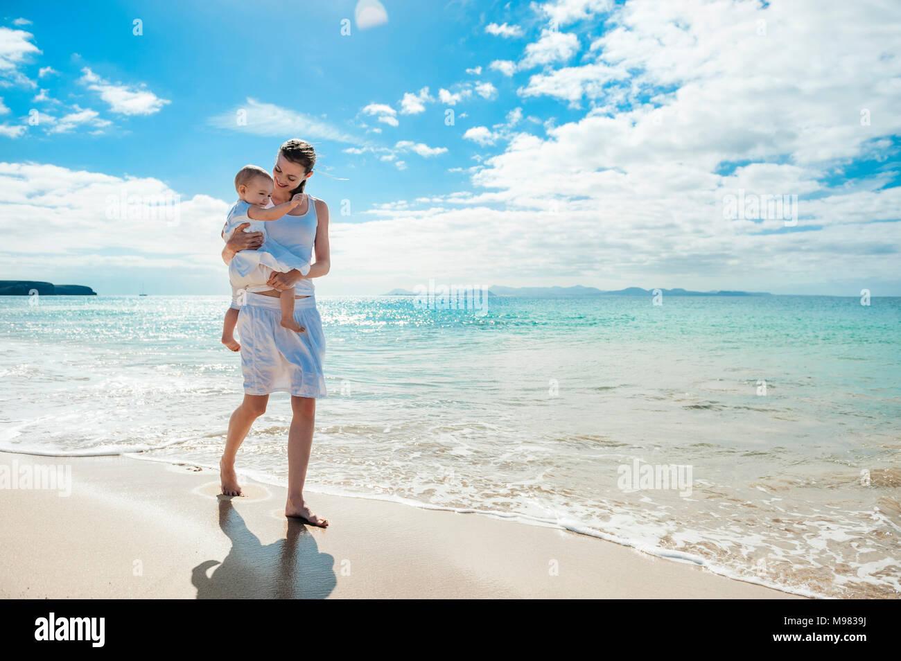 Madre camminando con la piccola figlia sulla spiaggia Immagini Stock