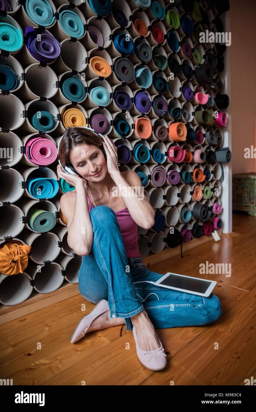 Rilassata donna matura ascoltando la musica di fronte all'assortimento di tappeti di yoga Immagini Stock