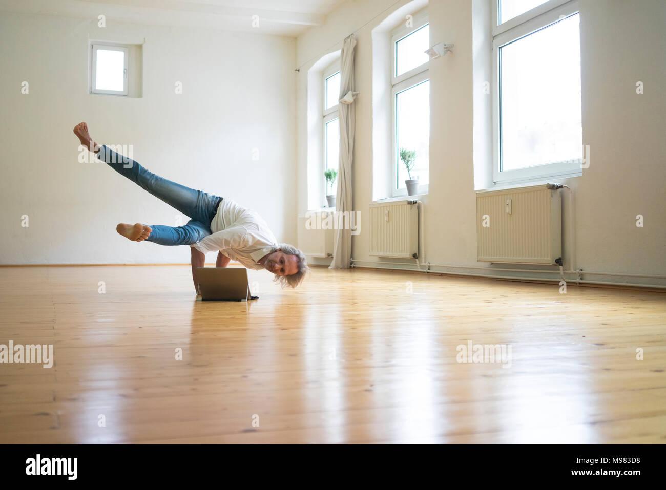 Uomo maturo facendo un handstand sul pavimento nella stanza vuota guardando tablet Immagini Stock