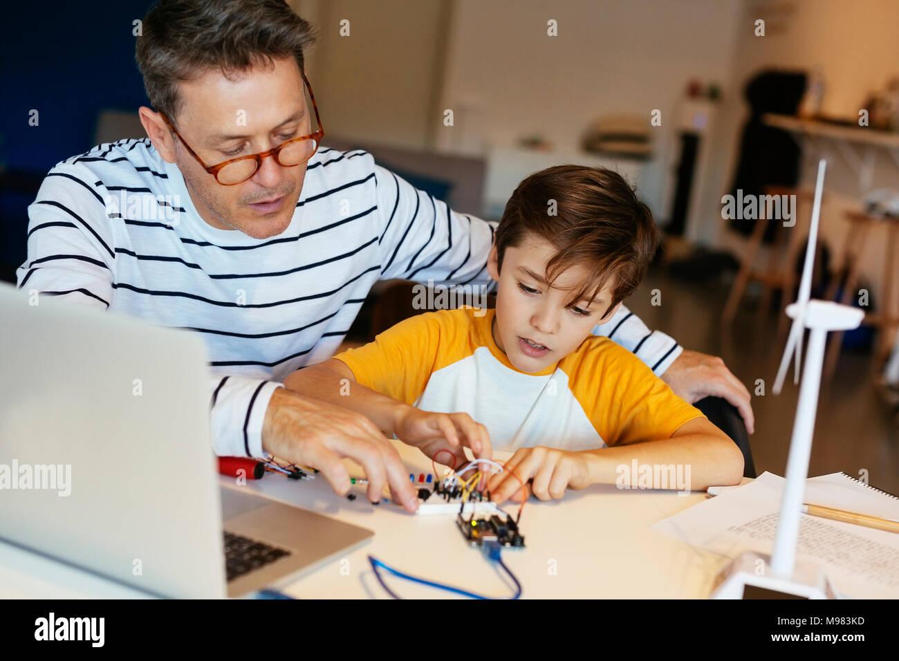 Padre e figlio il montaggio di un kit di costruzione con il computer portatile e la turbina eolica modello Immagini Stock